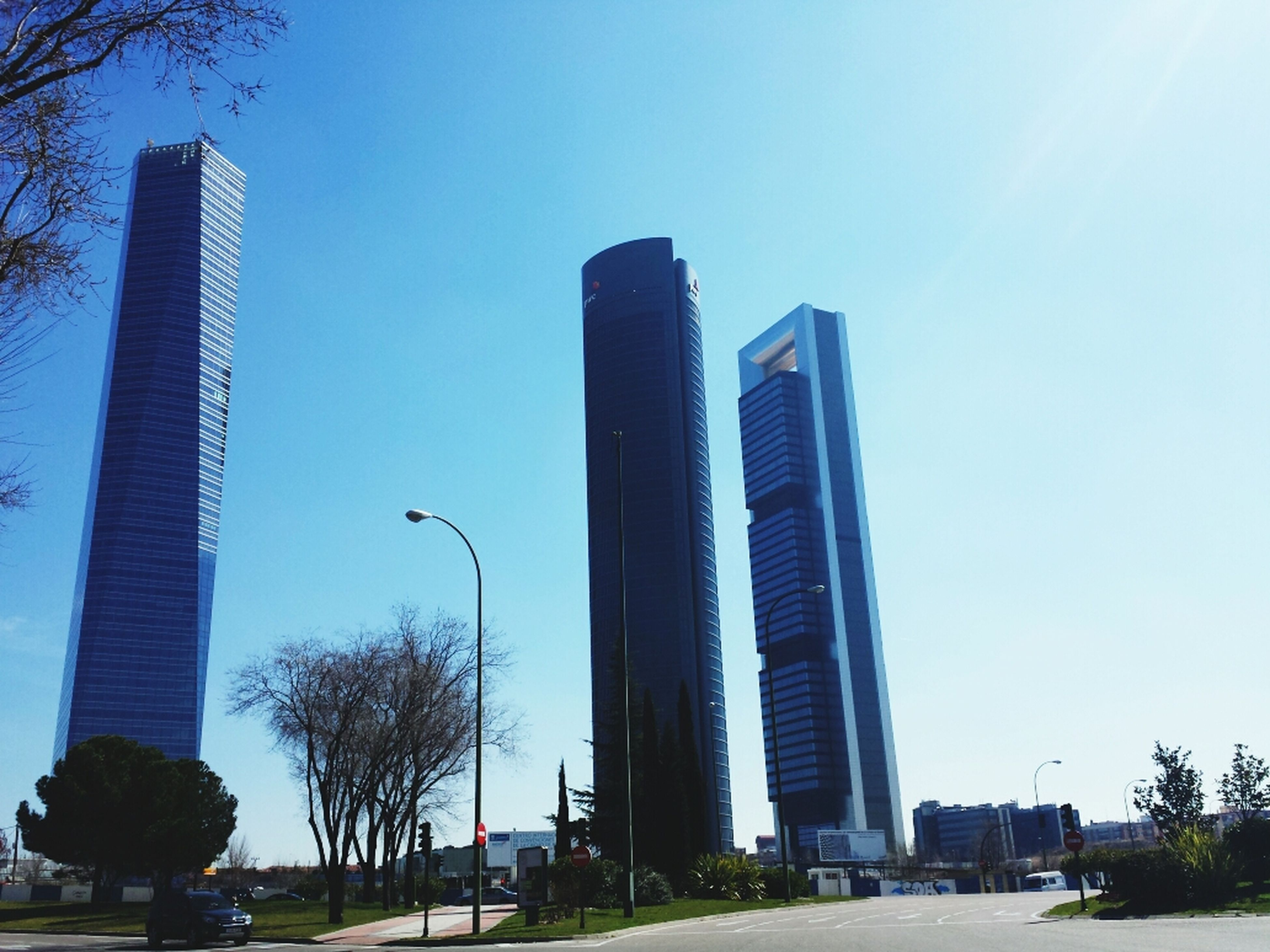 building exterior, architecture, built structure, skyscraper, city, tall - high, clear sky, modern, office building, tower, tree, low angle view, car, urban skyline, transportation, city life, blue, building, tall, street light