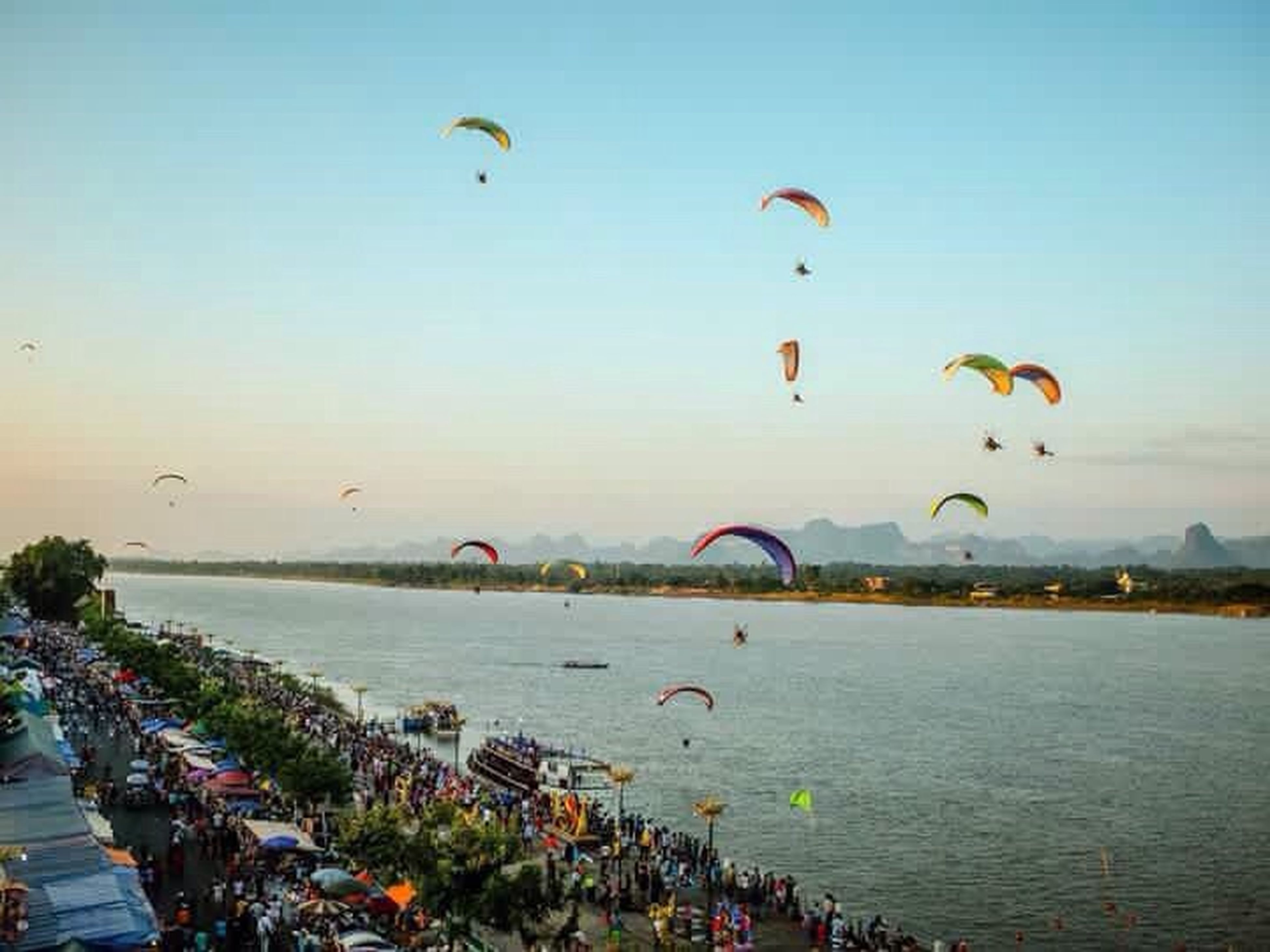 flying, mid-air, water, sea, bird, parachute, transportation, nature, paragliding, tranquility, outdoors, multi colored, scenics, waterfront, blue, day, large group of objects, sky, tranquil scene, mountain, vacations