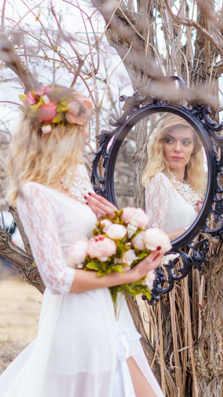 wedding dress, bride, wedding, flower, white color, young women, real people, young adult, celebration, bouquet, one person, holding, day, outdoors, groom, standing, life events, women, happiness, headdress, blond hair, fragility, bridegroom, close-up, nature, people