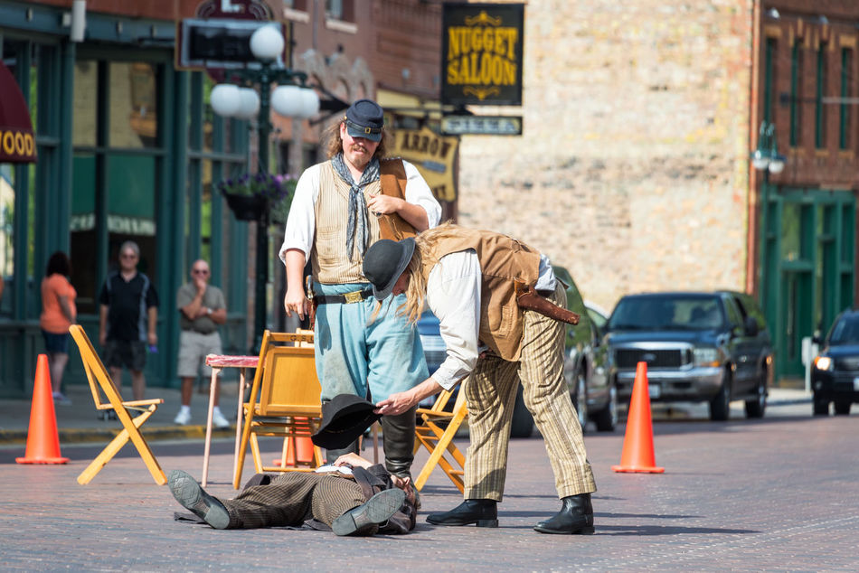 DEADWOOD, SD - AUGUST 26: Actors reenact a gunfight in Deadwood, SD on August 26, 2015 Actors Architecture Bar Black Hills Casino Deadwood  Downtown Gunfight Historic Hotel Old West  People Reenactment Restaurant South Dakota Tavern  Tourism Tourists Town Travel Travel Destinations Two People USA Western Wild West
