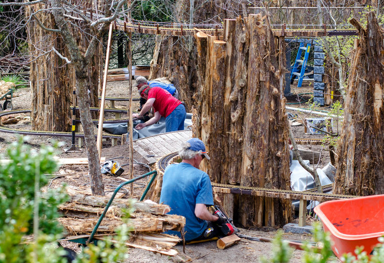 workers help recreate a miniature railroad in a local garden, after a fire destroyed the original train village Train Tracks Adult Adults Only Building Model Railroad Craftsmen Day Garden Project Manual Worker Men Miniature Trains Nature Outdoors Park People Real People Restoration In Progress Tools Working