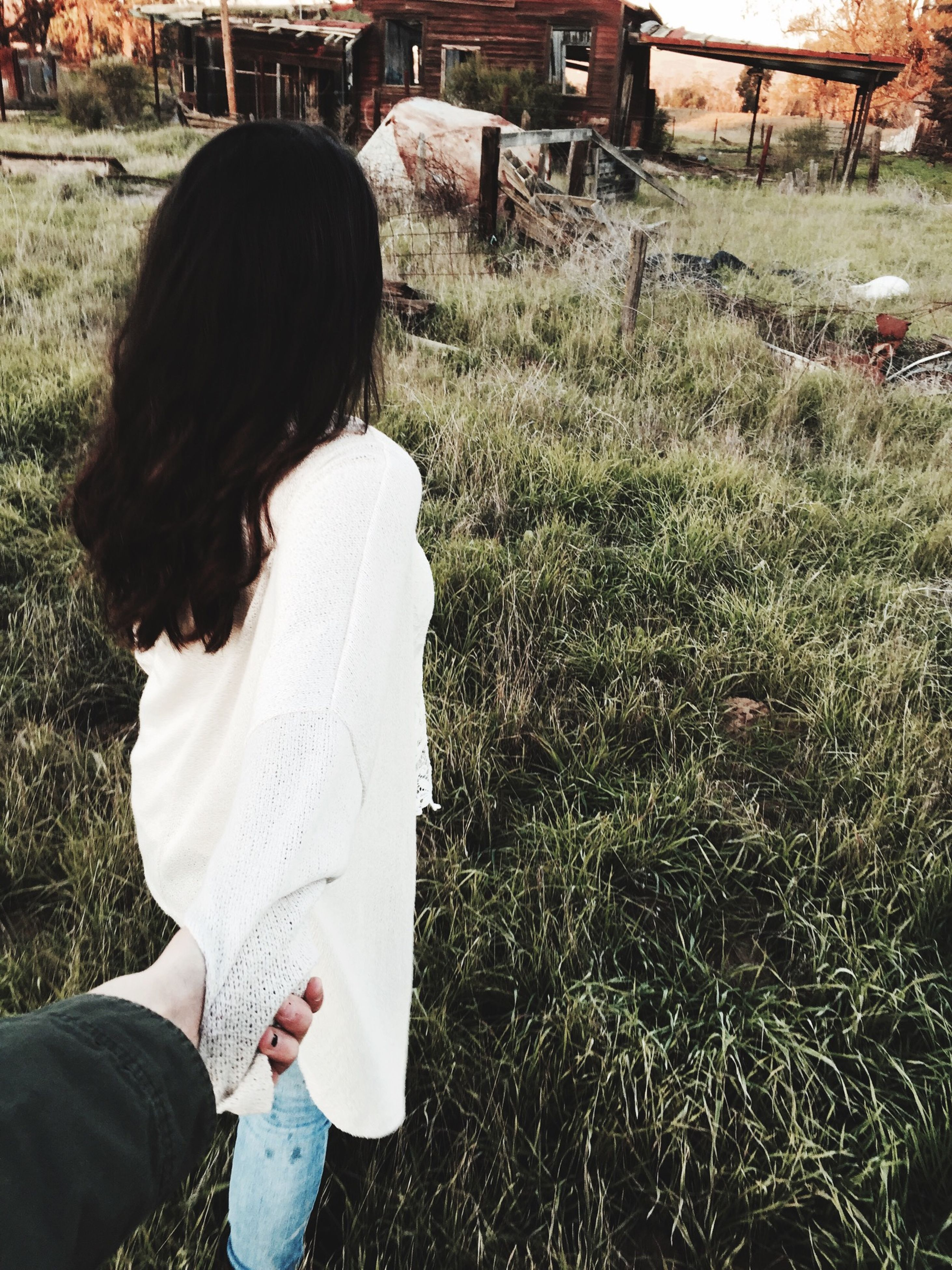 lifestyles, leisure activity, grass, field, casual clothing, rear view, girls, childhood, holding, person, standing, elementary age, day, grassy, three quarter length, focus on foreground, outdoors, waist up