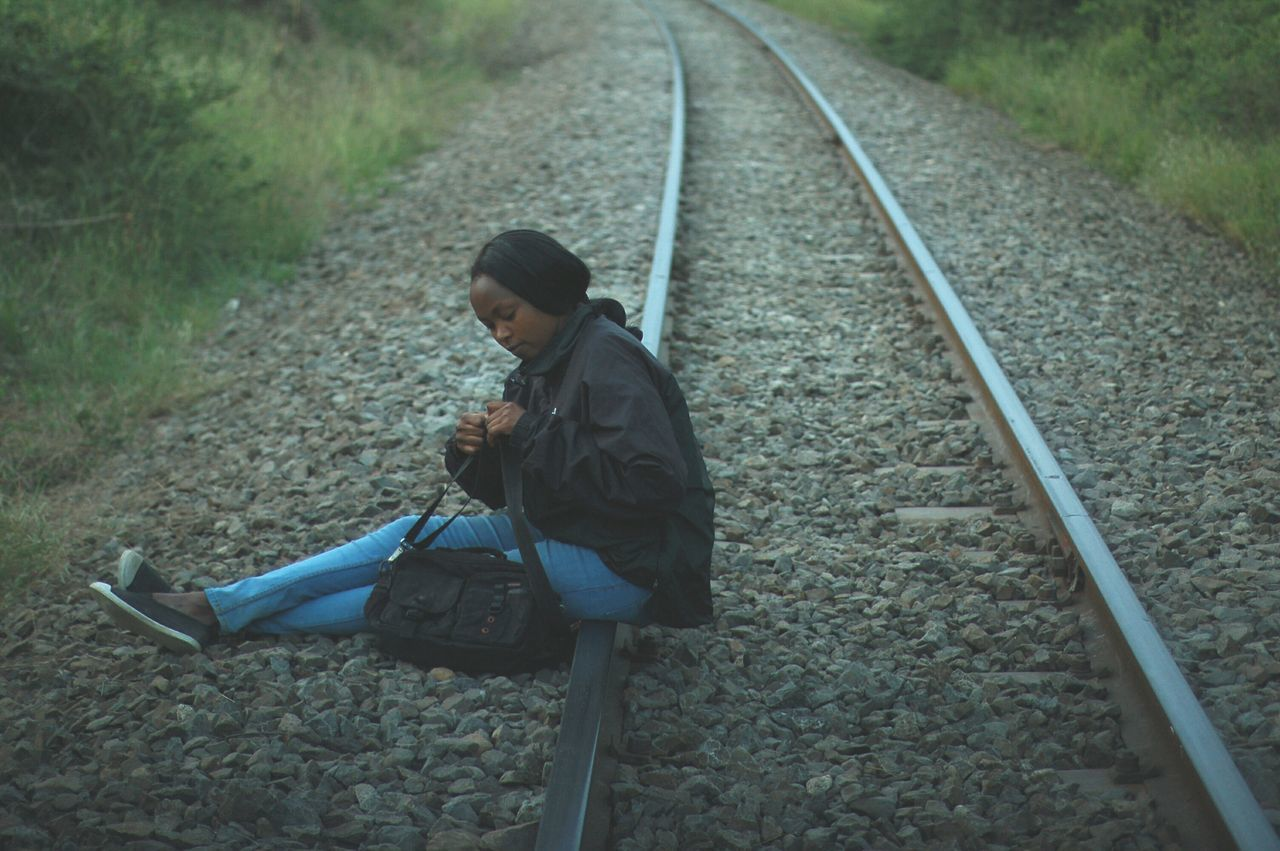 railroad track, transportation, rail transportation, one person, real people, full length, side view, leisure activity, outdoors, day, lifestyles, adventure, nature, young adult, people