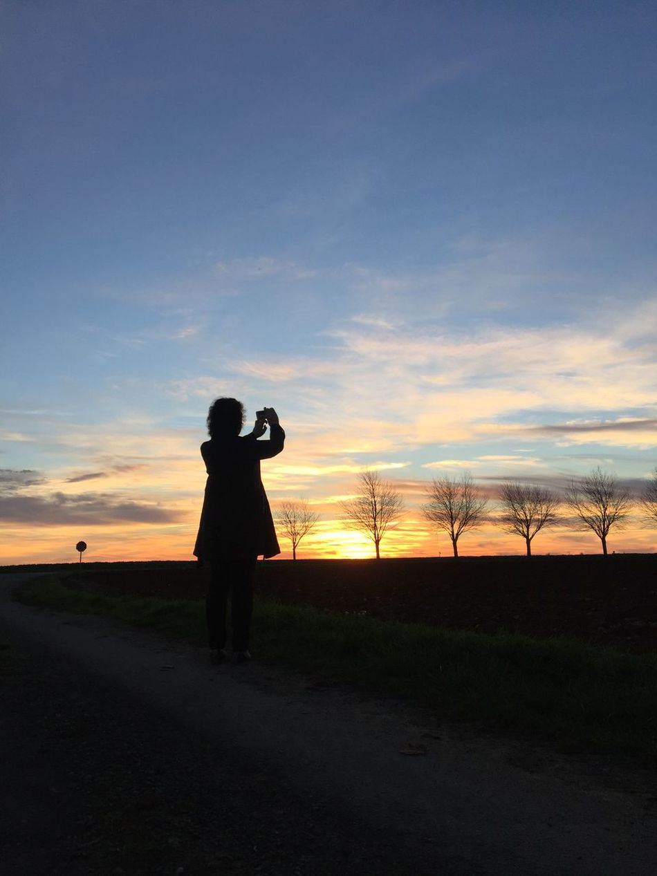 Sunset Sky Standing Photography Themes Real People Leisure Activity Lifestyles One Person Silhouette Men Camera - Photographic Equipment Outdoors Nature Field Scenics Beauty In Nature One Man Only Day Adult Mobile Conversations