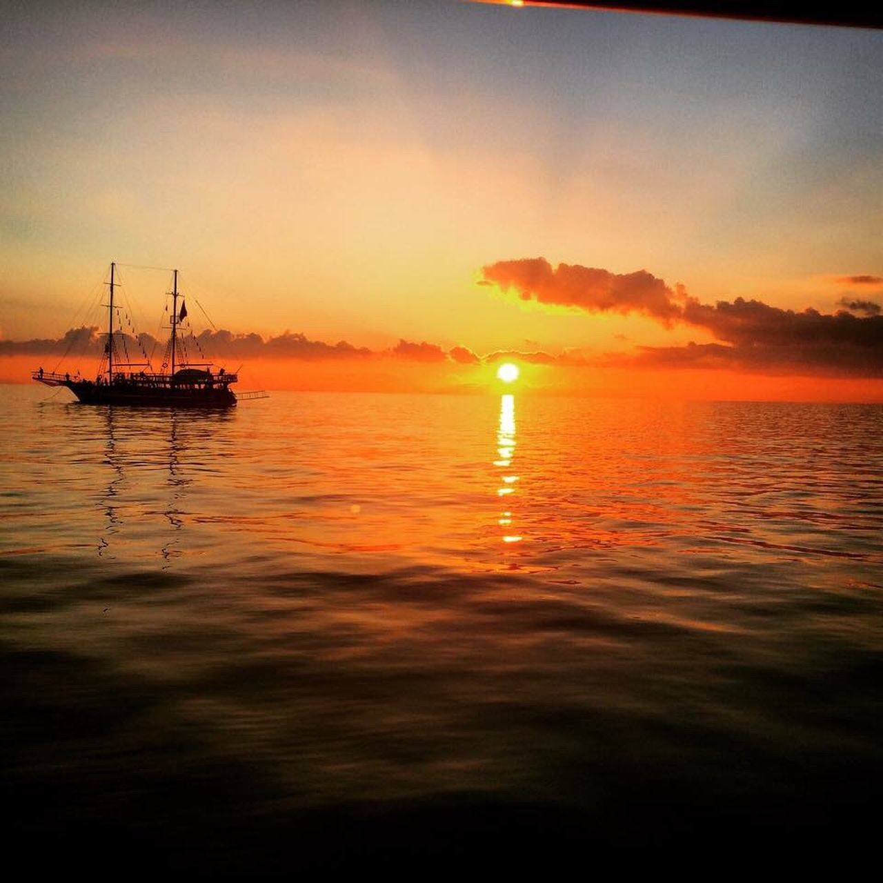 sunset, water, sea, nature, beauty in nature, scenics, tranquility, orange color, sky, nautical vessel, waterfront, outdoors, tranquil scene, silhouette, reflection, no people, transportation, mast, horizon over water, day
