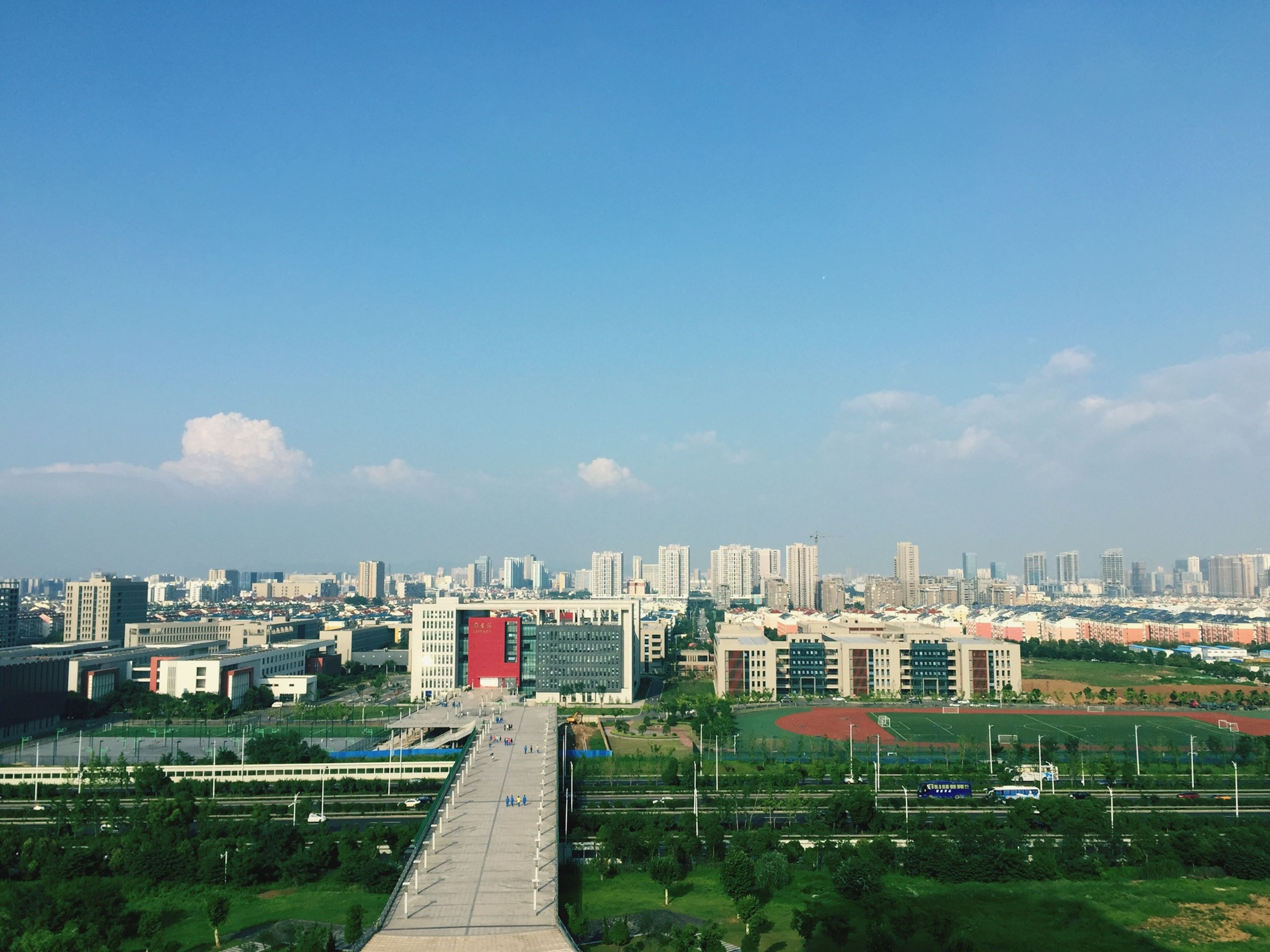 building exterior, architecture, built structure, city, cityscape, sky, blue, the way forward, high angle view, residential structure, road, residential district, residential building, tree, copy space, day, outdoors, diminishing perspective, transportation, no people