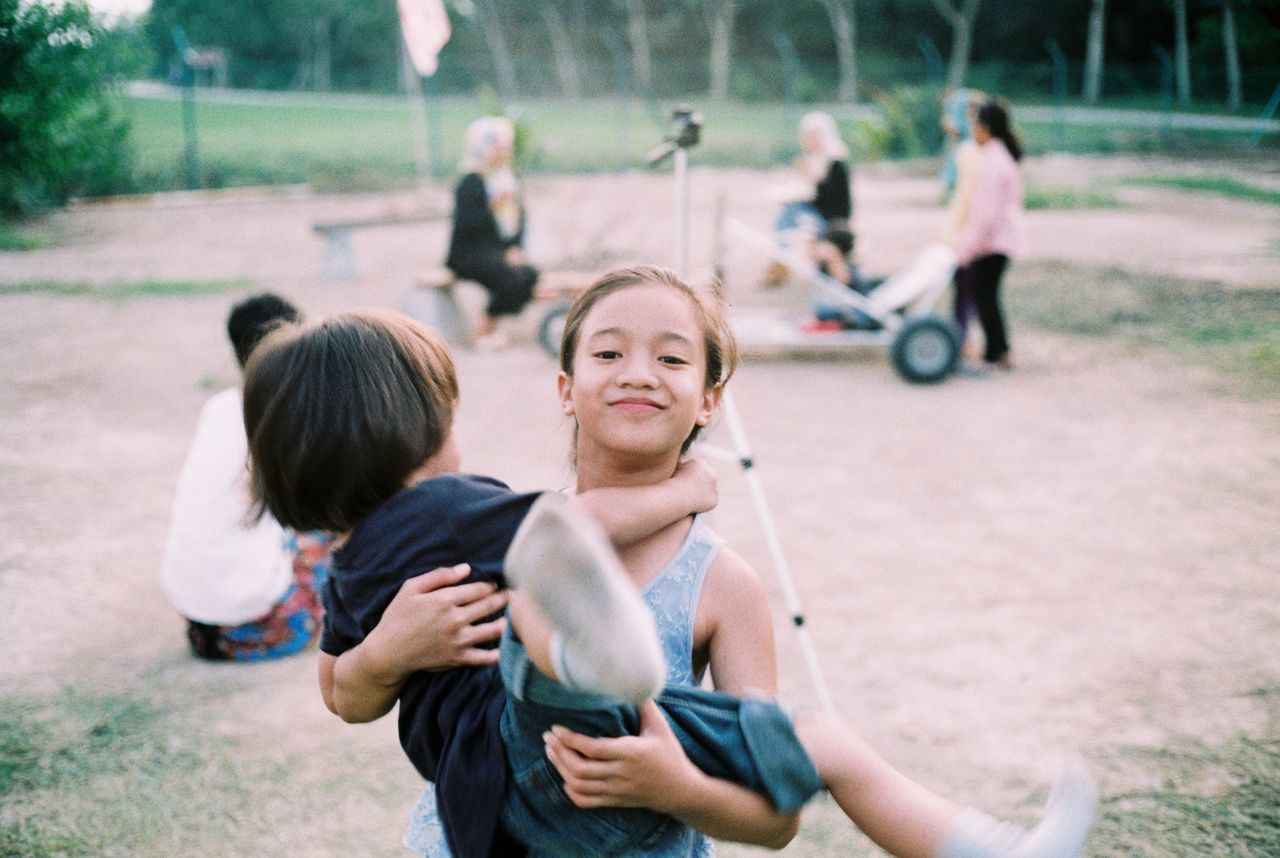 real people, childhood, leisure activity, girls, lifestyles, day, focus on foreground, boys, park - man made space, casual clothing, togetherness, playing, outdoors, holding, two people, technology