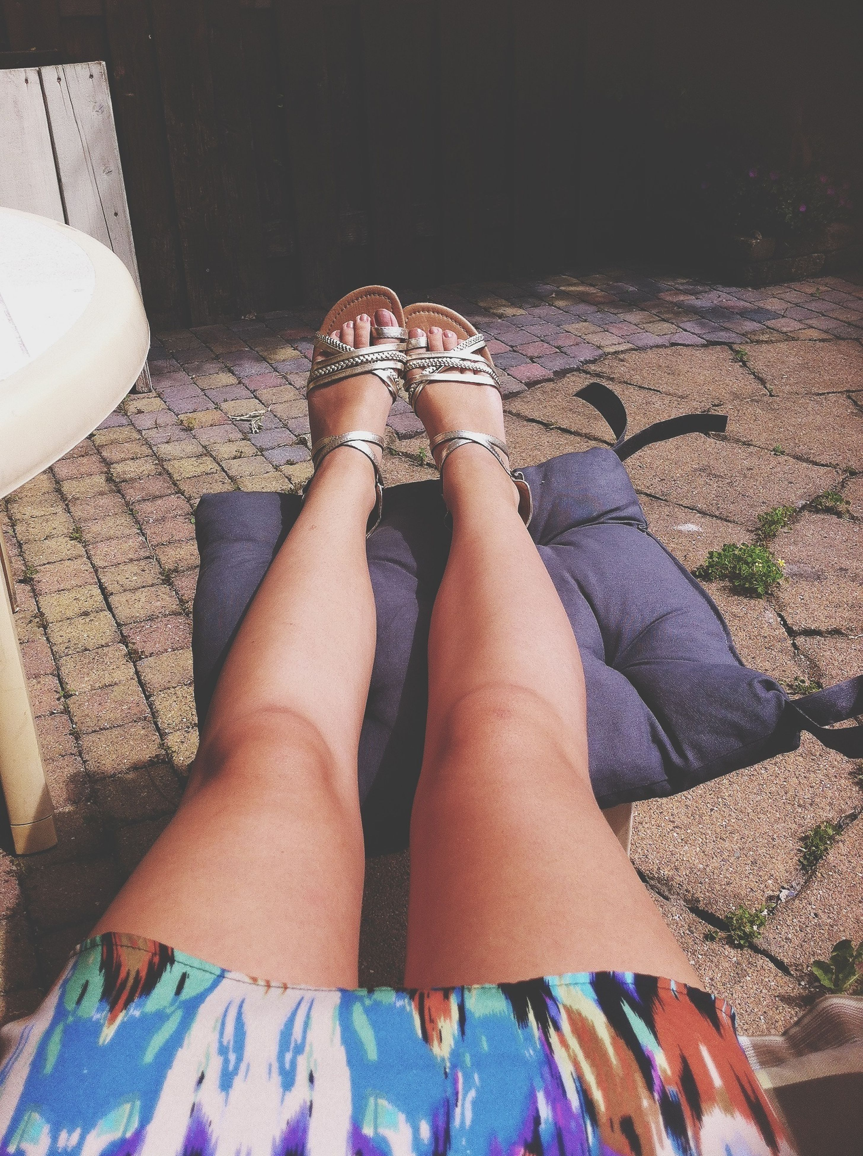 low section, person, personal perspective, lifestyles, shoe, relaxation, sitting, leisure activity, human foot, high angle view, footwear, jeans, casual clothing, legs crossed at ankle, sunlight, standing