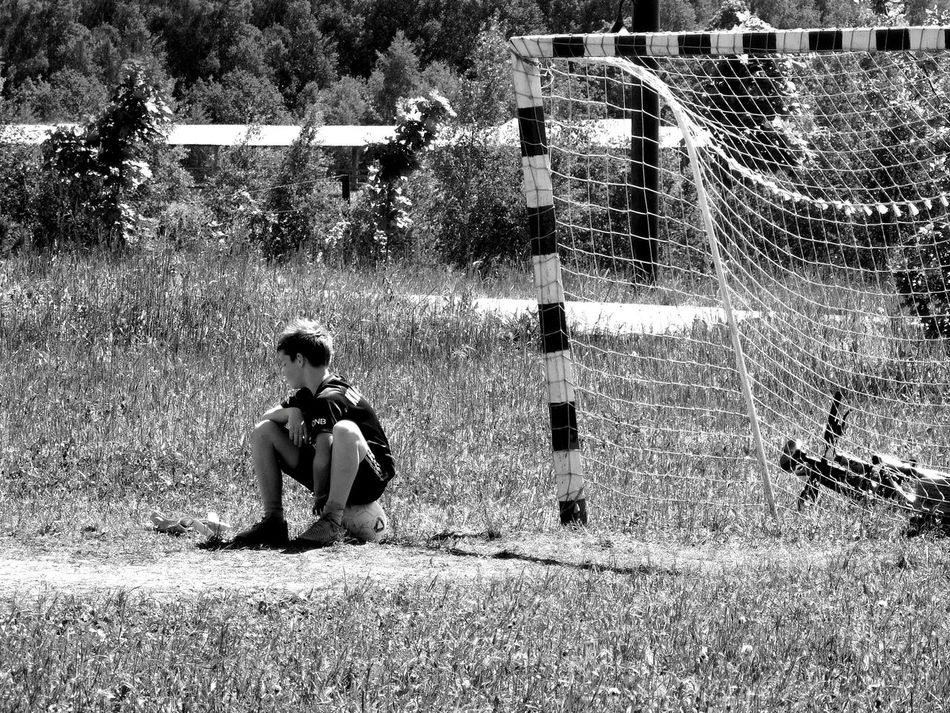 Ball Blackandwhite Boys Bycicle Childhood Day Football Full Length Grass Leisure Activity Lifestyles Nature One Boy Only One Person Outdoors People Playing Real People Sitting Sport Summer Tree Unrecognizable Person