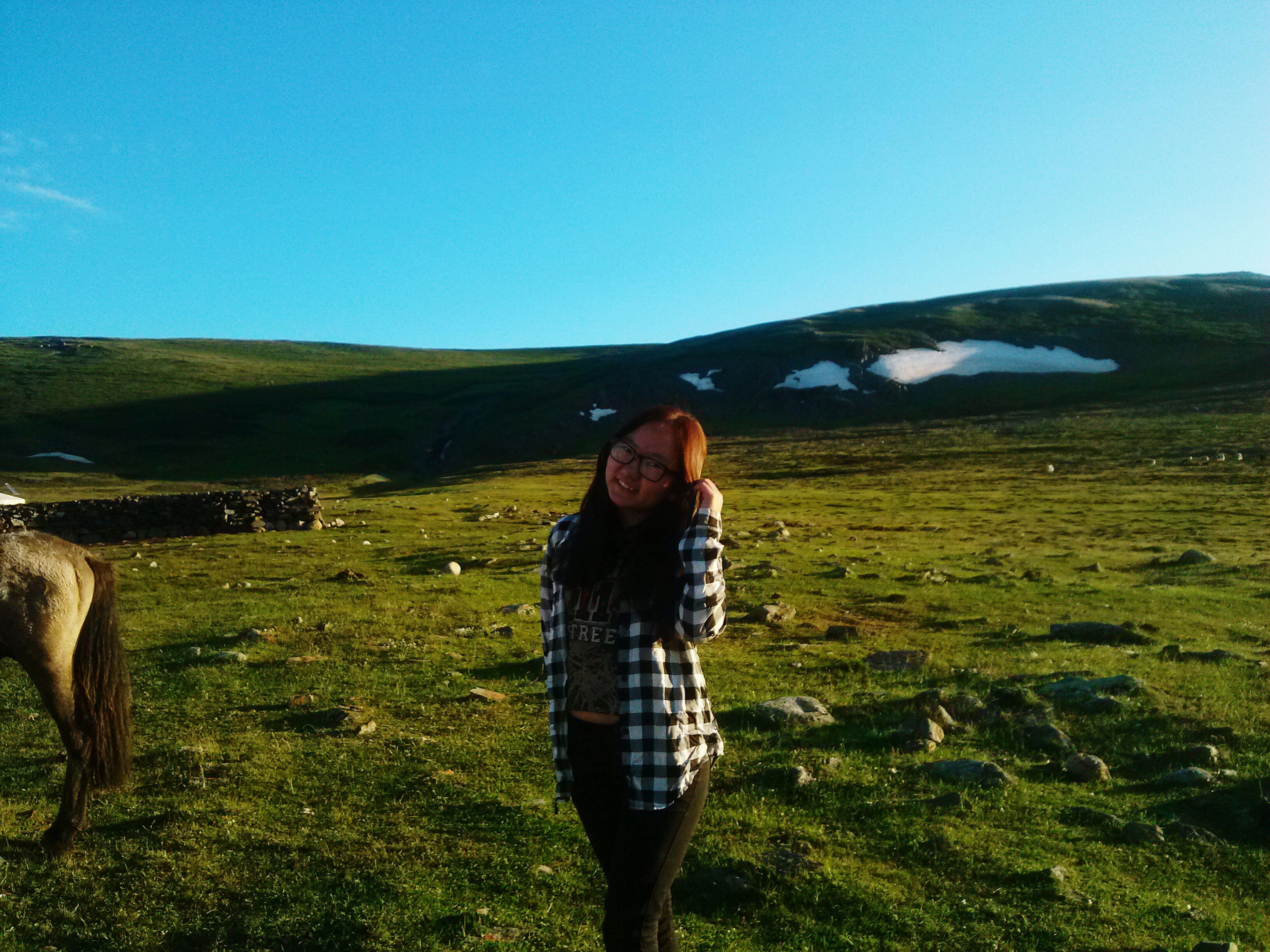 clear sky, leisure activity, standing, young adult, mountain, young women, lifestyles, casual clothing, person, blue, tranquil scene, scenics, long hair, beauty, nature, beauty in nature, tranquility, field, green color, vacations, mountain range, non-urban scene, day