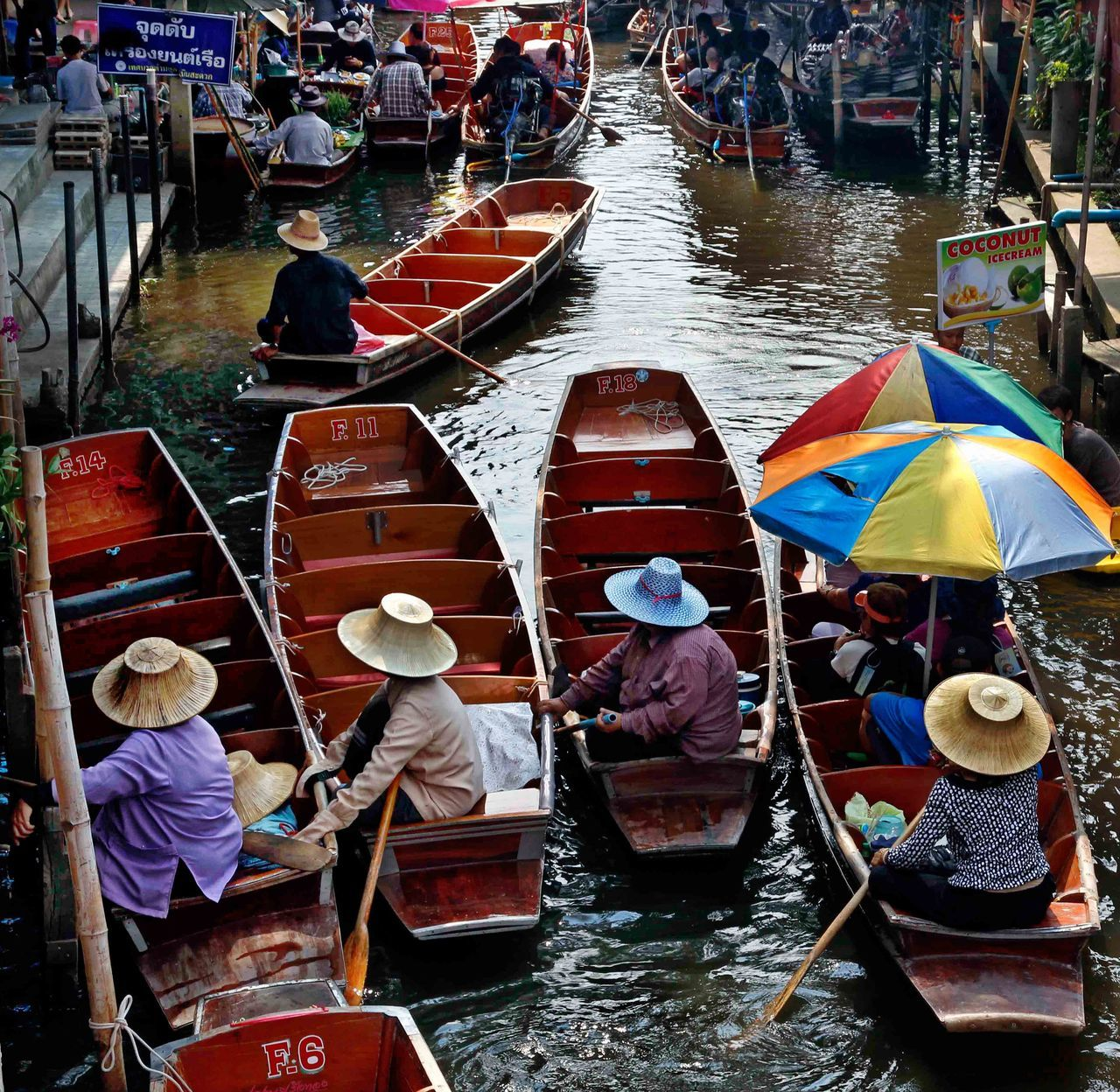 nautical vessel, transportation, water, boat, men, canal, oar, real people, rowing, mode of transport, women, day, moored, high angle view, large group of people, asian style conical hat, rowboat, sitting, outdoors, occupation, gondolier, canoe, wooden raft, lake, sailing, harbor, gondola - traditional boat, adult, people