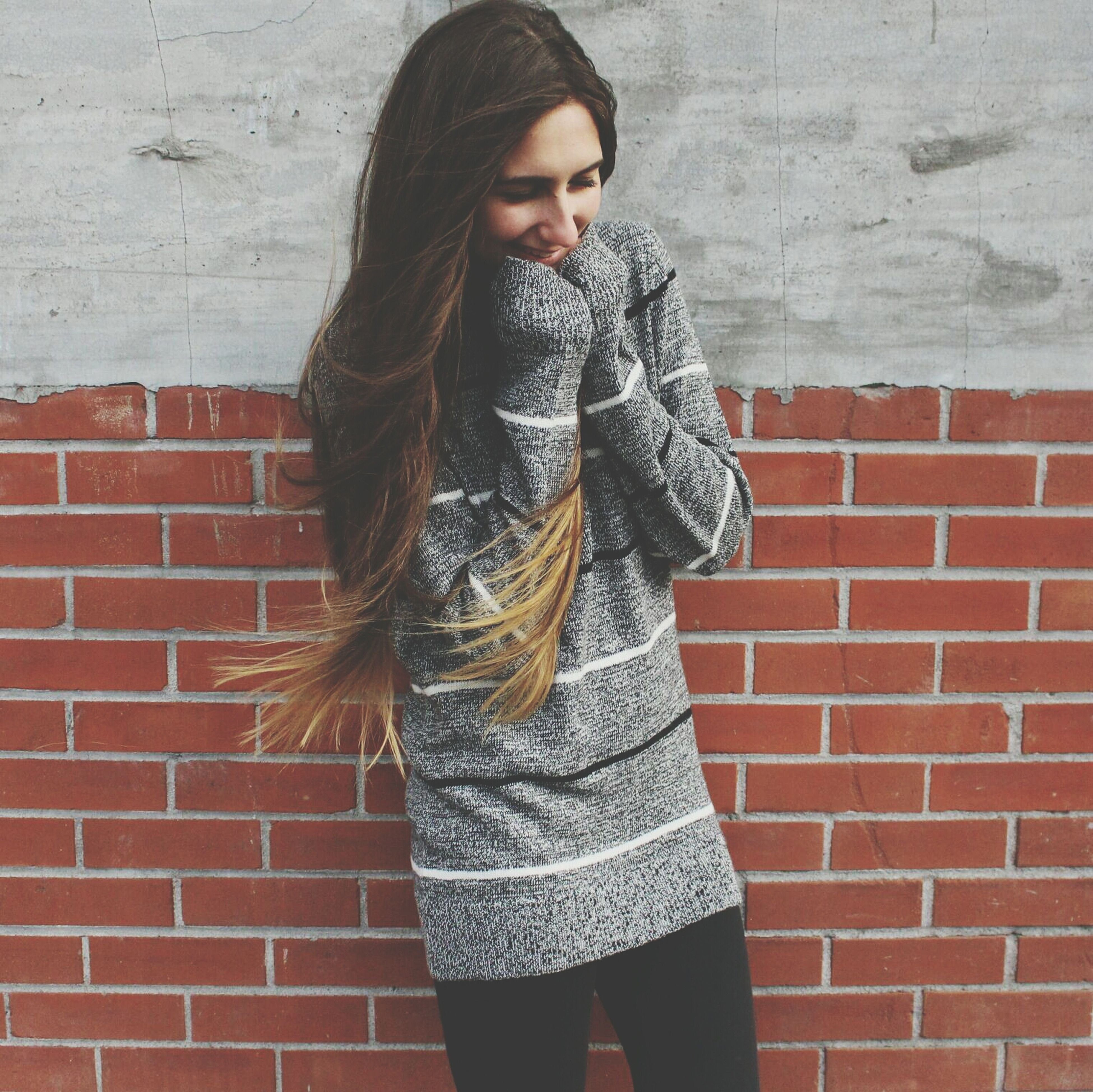 casual clothing, young adult, standing, person, young women, front view, lifestyles, wall - building feature, brick wall, portrait, looking at camera, long hair, three quarter length, leisure activity, fashionable, jacket, wall