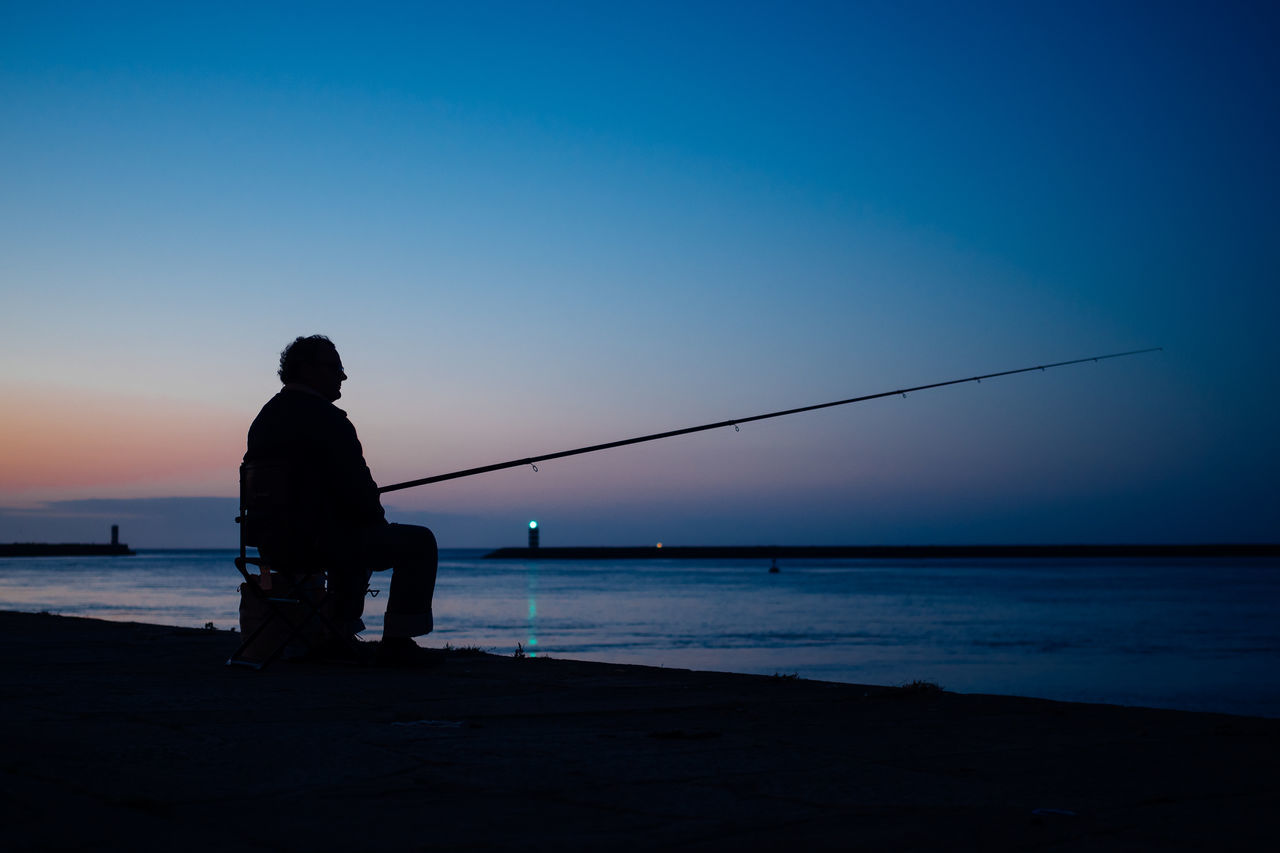 fisherman @ night Beauty In Nature Blue Fishing Fishing Pole Fishing Rod Fishing Tackle Fivedaysporto Full Length Horizon Over Water Leisure Activity Lifestyles Men Nature One Person Real People Scenics Sea Silhouette Sky Standing Sunset Tranquil Scene Tranquility Water Weekend Activities