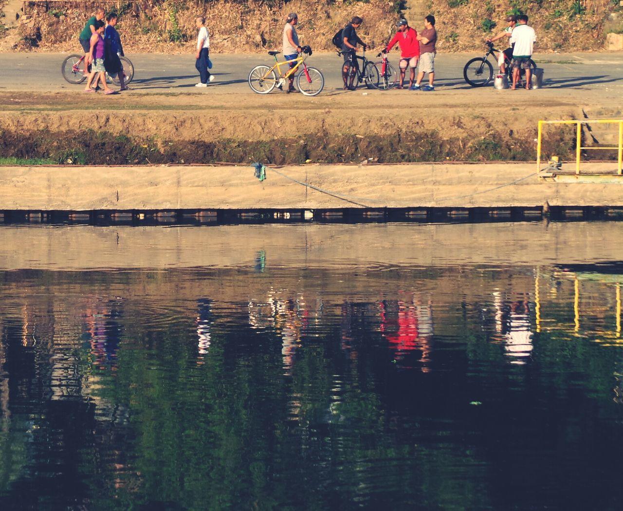 Bicyclists At Riverbank