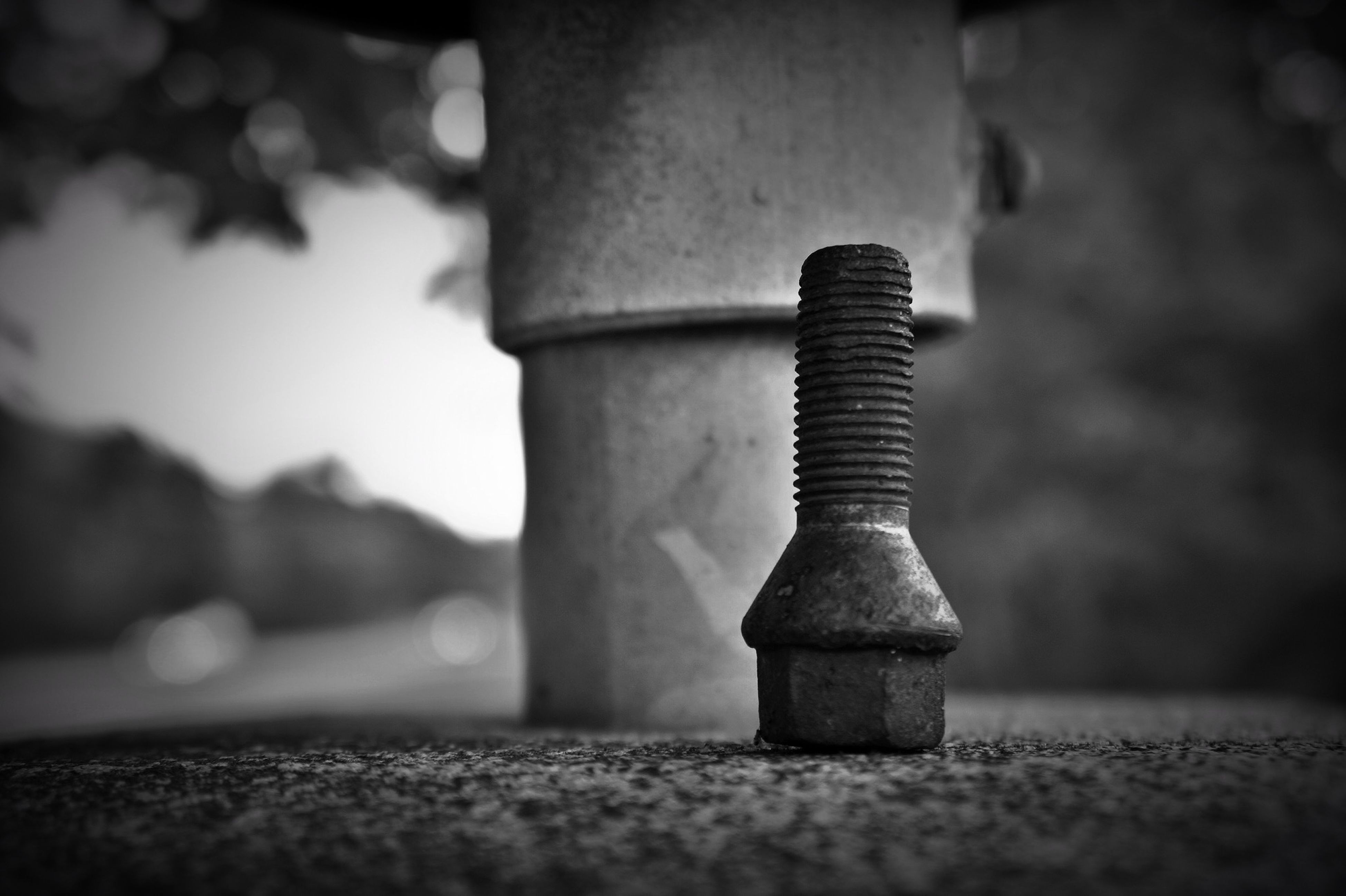 selective focus, focus on foreground, close-up, metal, surface level, still life, metallic, no people, textured, sunlight, day, outdoors, single object, shadow, wall - building feature, man made object, in a row, old, pole