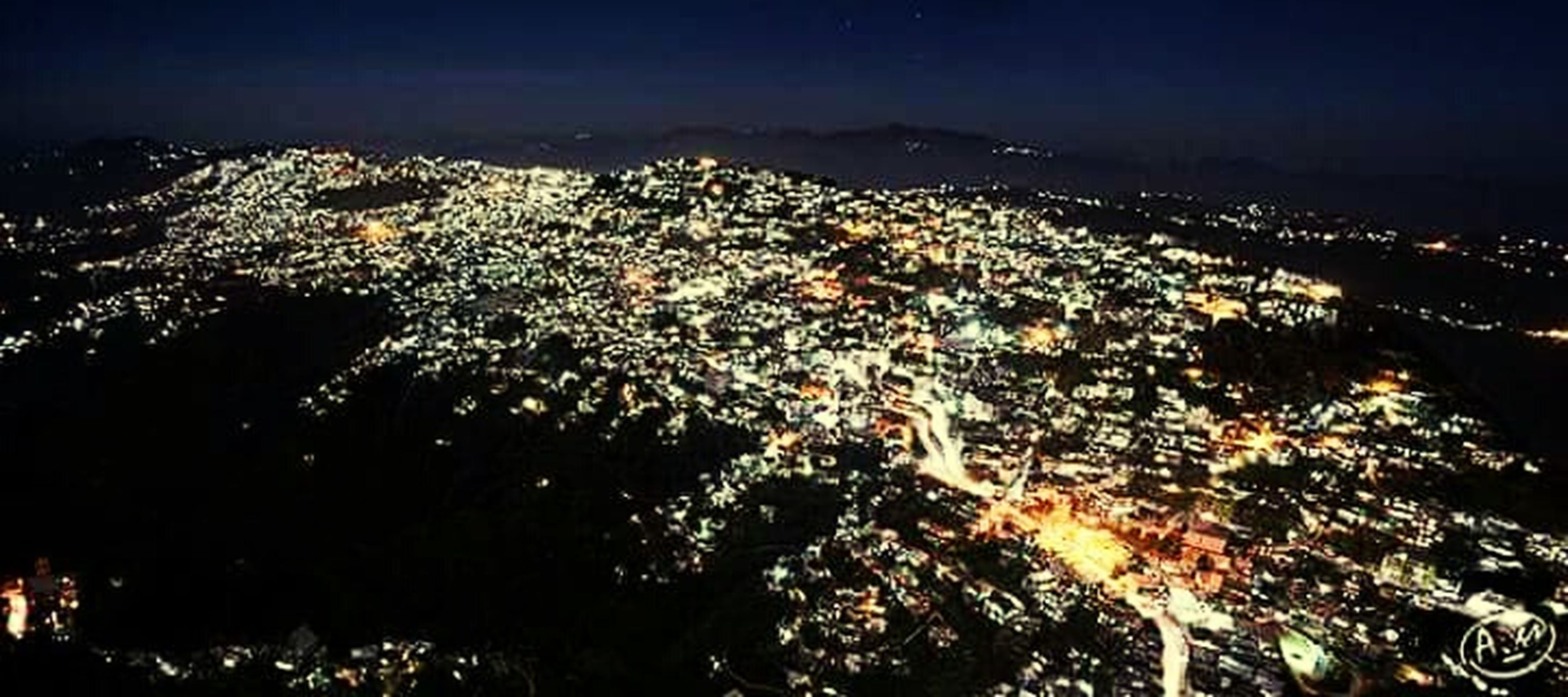 illuminated, night, cityscape, city, aerial view, crowded, high angle view, building exterior, architecture, built structure, residential district, sky, residential building, city life, residential structure, community, outdoors, sea, no people, elevated view