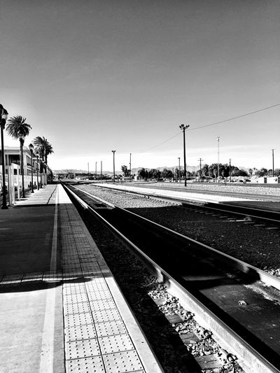 """What These Tracks Have Seen"" Historic railroad tracks now owned by the BNSF Railways, run in front of the historic Fred Harvey House 'El Garces' seen in the left background, parallel to Route 66 in Needles, California, USA. Railroad Tracks BNSF Trains El Garces Traintracks Historical Place Historic Route 66 Blackandwhite Photography Black And White Blackandwhite Harvey House"