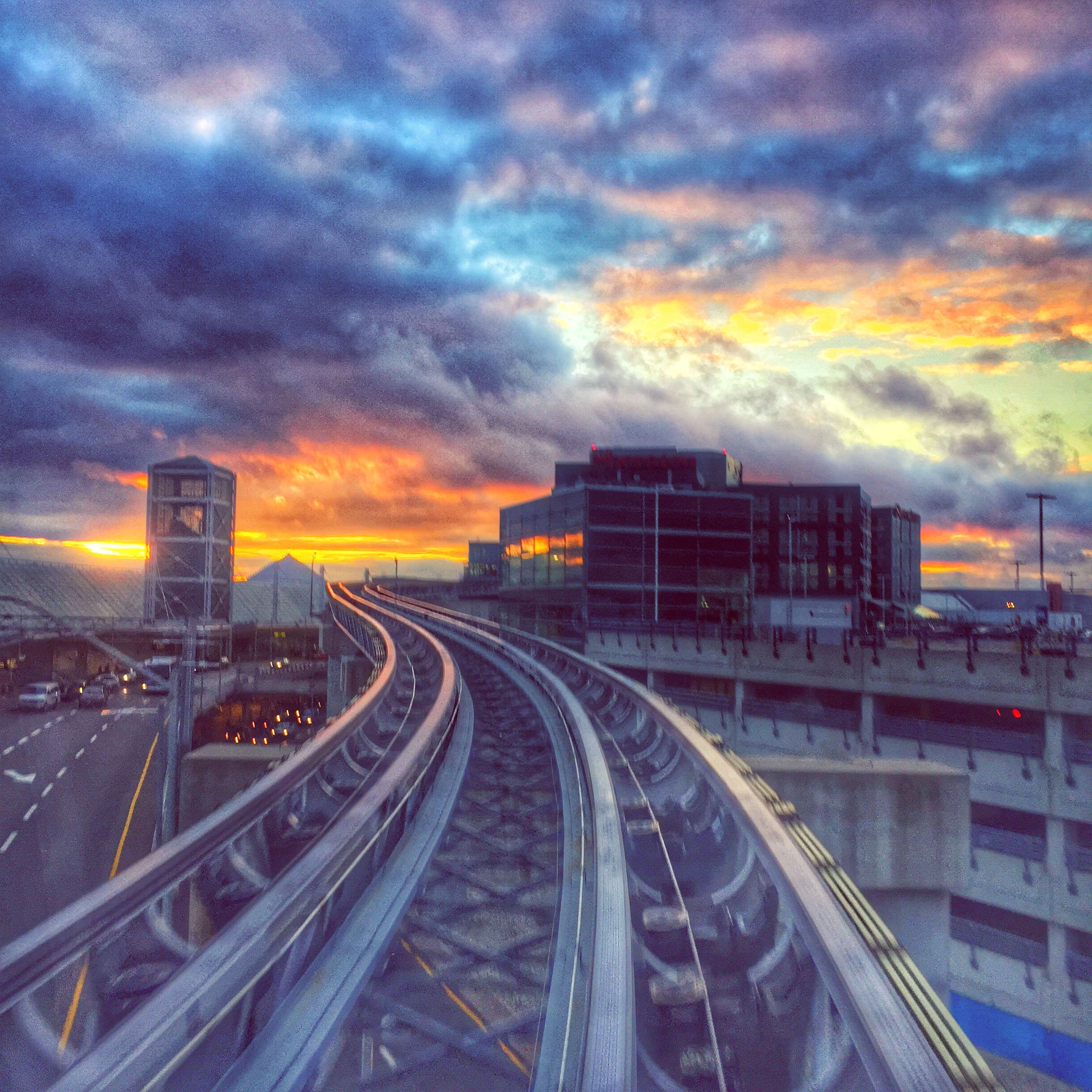 cloud - sky, sky, cloudy, sunset, architecture, weather, transportation, built structure, railroad track, building exterior, dramatic sky, overcast, the way forward, storm cloud, cloud, rail transportation, diminishing perspective, dusk, city, orange color