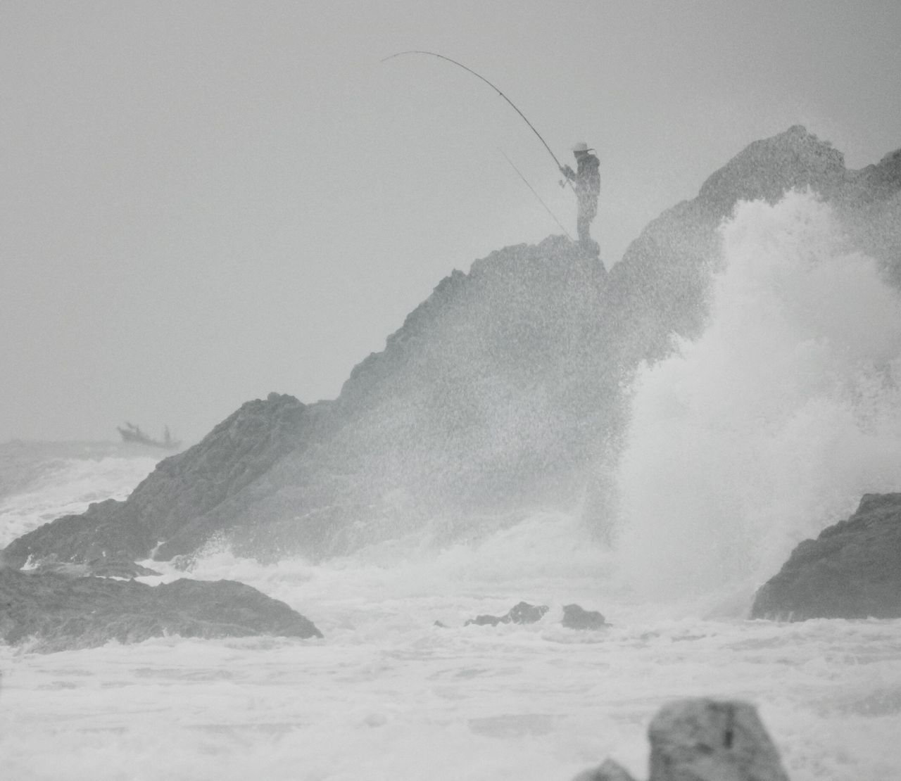 Side View Of Man Fishing In Sea At Dusk