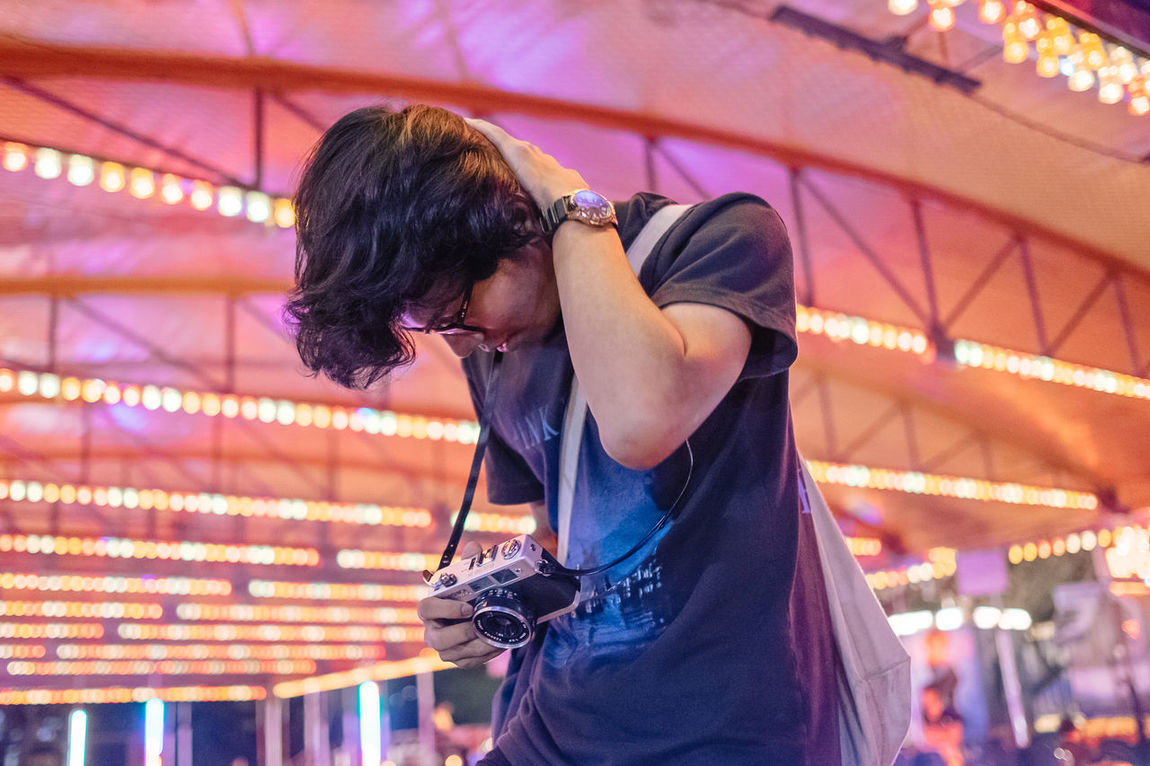 Camera Amusement Park Arts Culture And Entertainment Casual Clothing Film Camera Focus On Foreground Illuminated Indoors  Leisure Activity Lifestyles Neon Night One Person People Real People Young Adult