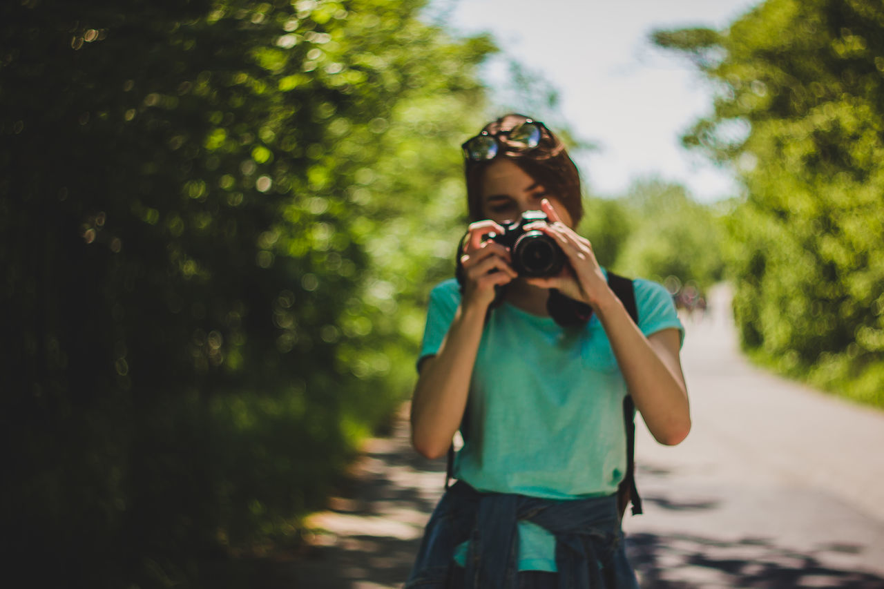 Young Woman Photographing On Road