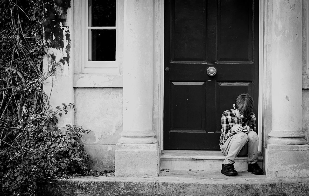 Even the young ones sneak off to check their phones Mobile Conversations Hiding From The World Blackandwhite Blackandwhite Photography Black & White Looking At Phone Building Exterior Sitting Window Door One Person House Outdoors Built Structure Architecture Entrance Steps Front Door Day Front Stoop People Boy Streetphotography Street Photography