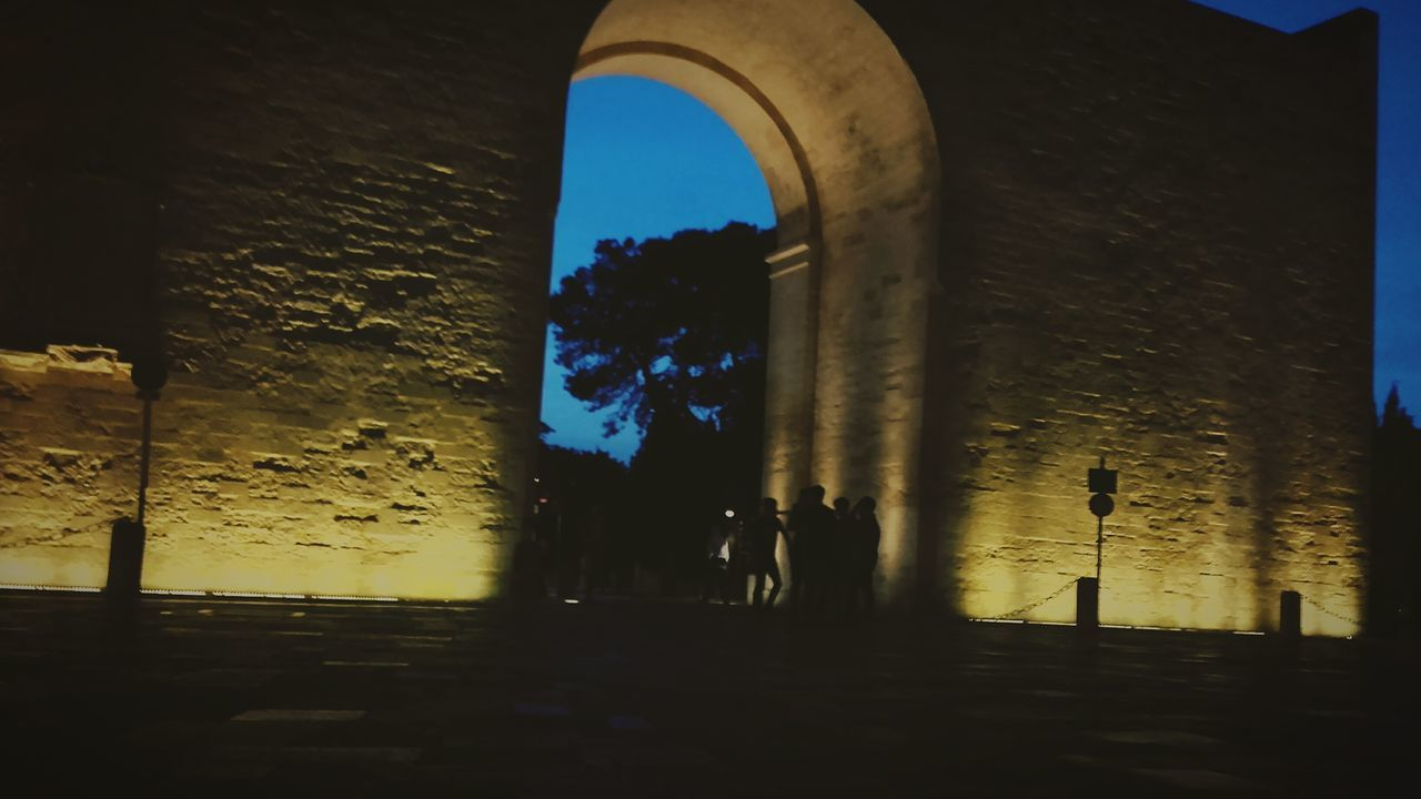 architecture, built structure, arch, history, building exterior, silhouette, old ruin, travel destinations, outdoors, night, city, sky, men, real people, ancient civilization, people