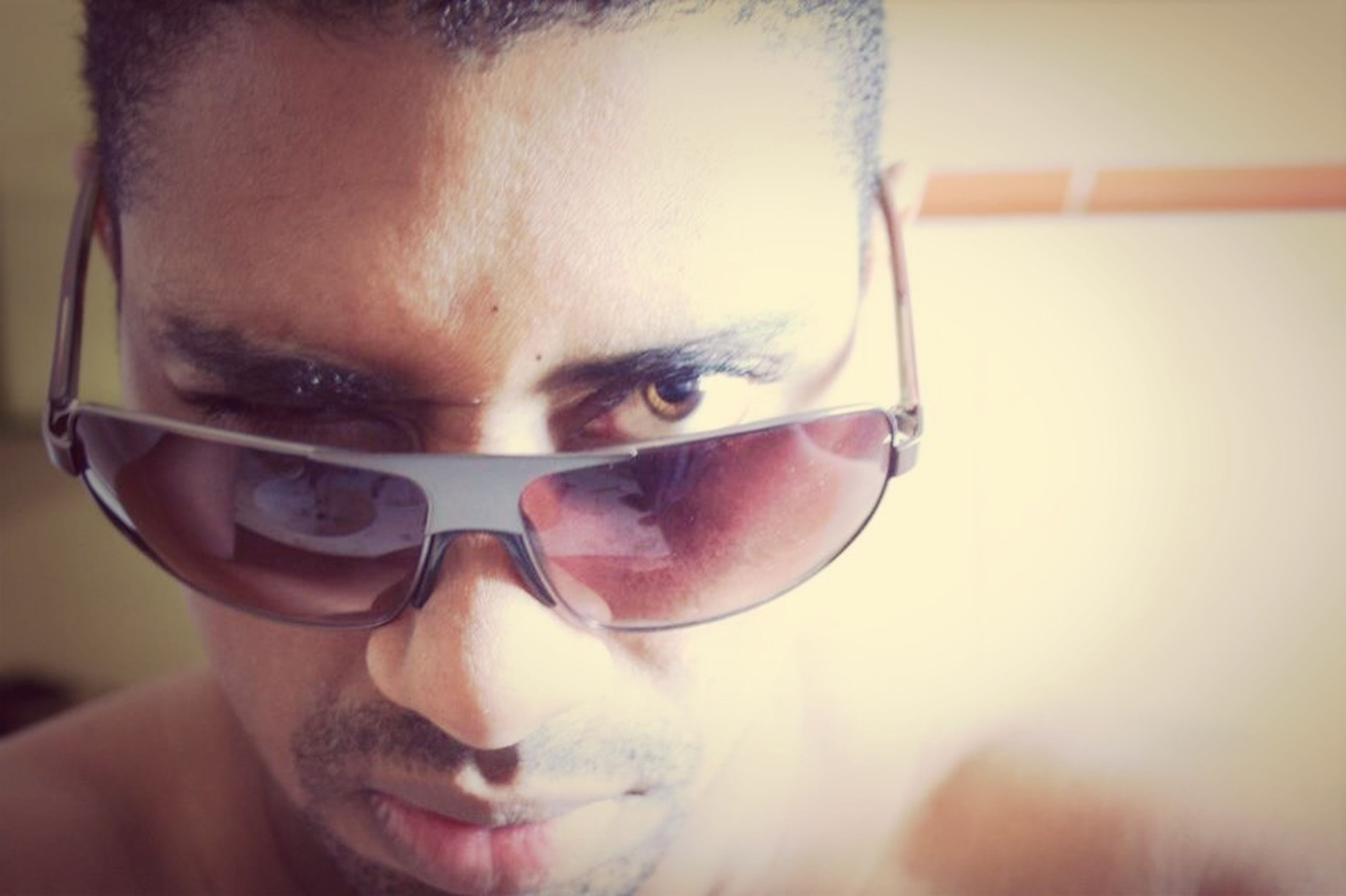 headshot, lifestyles, person, close-up, looking at camera, portrait, young adult, leisure activity, human face, front view, indoors, focus on foreground, head and shoulders, sunglasses, holding, young men