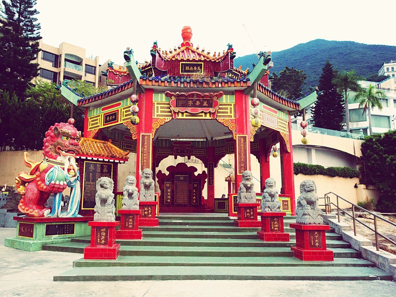 architecture, steps, built structure, building exterior, day, sculpture, outdoors, dragon, statue, tree, no people, sky, chinese dragon