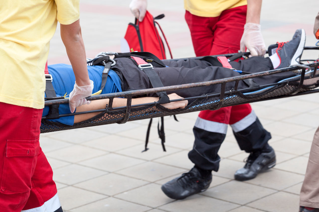 Midsection Of Men Carrying Patient On Stretcher