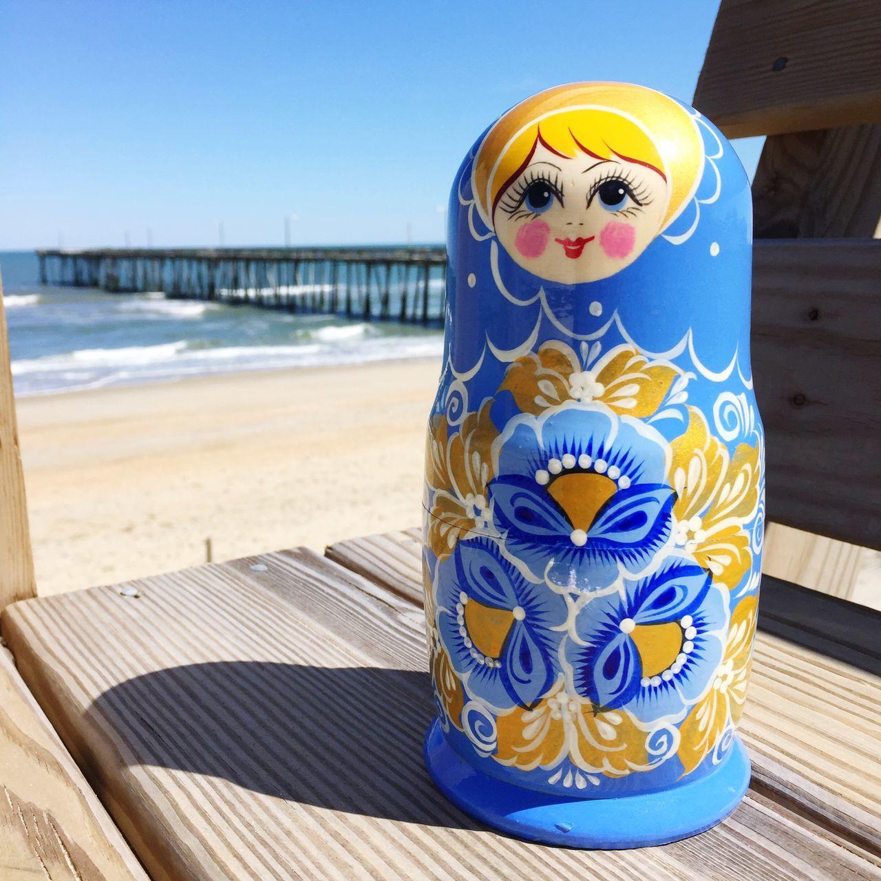 Matryoshka Doll On Bench At Beach Against Clear Blue Sky