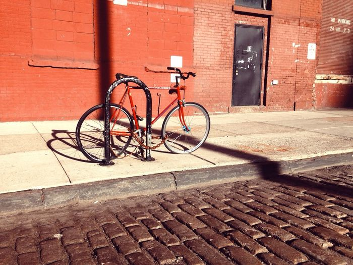 Still. Parked Bikes Bicycle Brick Wall Mode Of Transport Transportation Architecture Building Exterior Built Structure Stationary Outdoors Day Red Land Vehicle Sunlight City No People Shadow DUMBO, Brooklyn