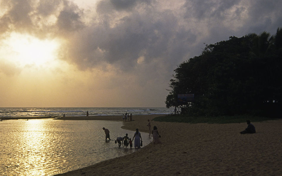 Local families enjoy a dip in the sea as the sun sets over Beruwela and bentota in Sri Lanka Beach Beauty In Nature Cloud - Sky Dusk Horizon Over Water Idyllic Leisure Activity Lifestyles Outdoors Scenics Sea Shore Silhouette Sky Sri Lanka Sunset Tranquil Scene Tranquility Unrecognizable Person Vacations Water