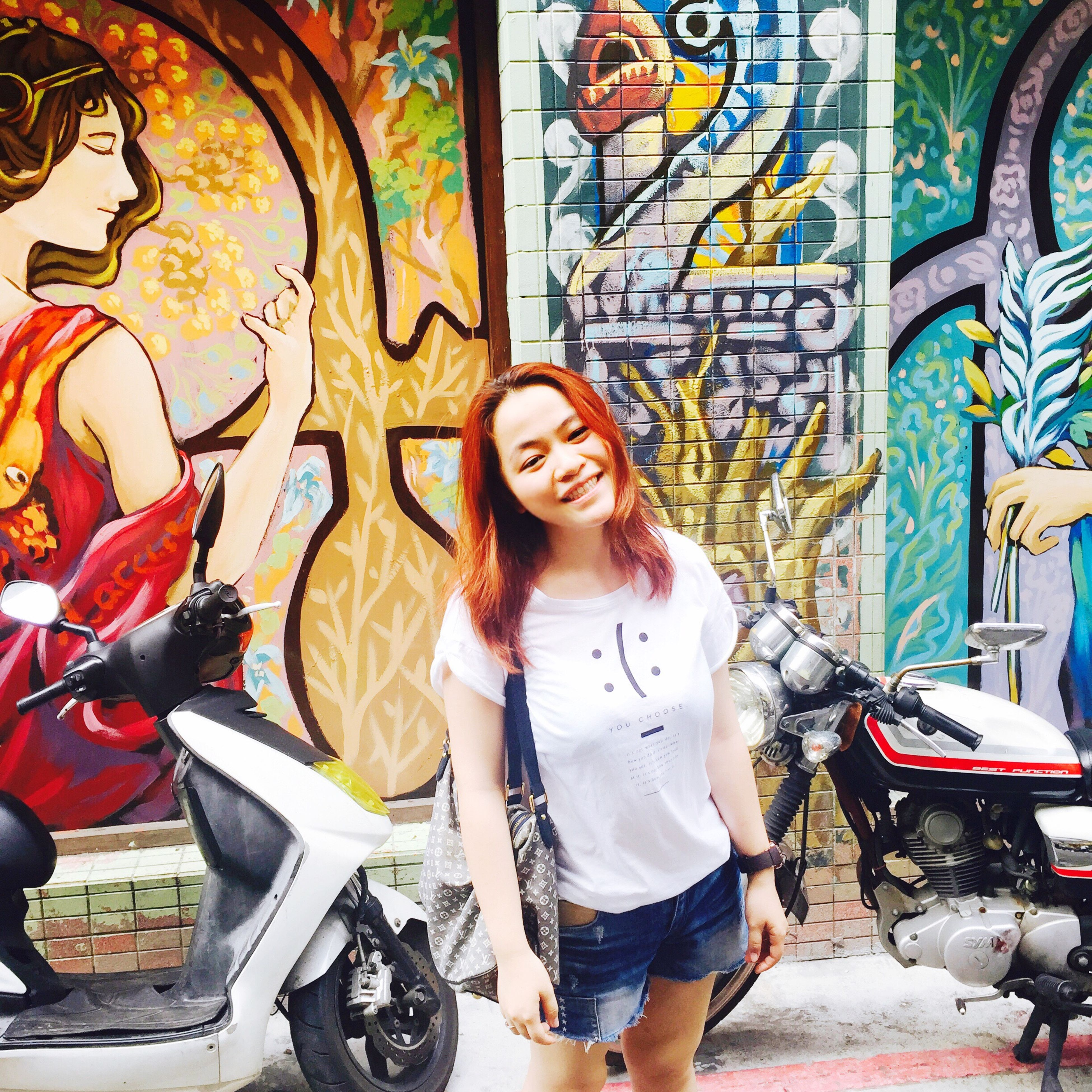 lifestyles, young adult, casual clothing, young women, leisure activity, person, looking at camera, front view, portrait, standing, graffiti, street, smiling, long hair, architecture, wall - building feature, happiness, built structure