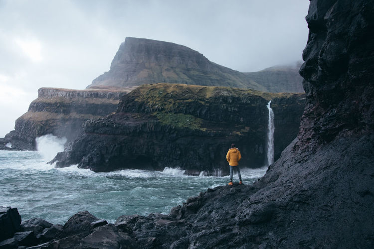 Faroe Islands Faroe Islands Scene Adventure Beauty In Nature Cliff Faroe Faroe Islands Men Mountain Nature One Person Outdoors Real People Rear View Rock - Object Rock Formation Sea Standing Water Waterfall Wave