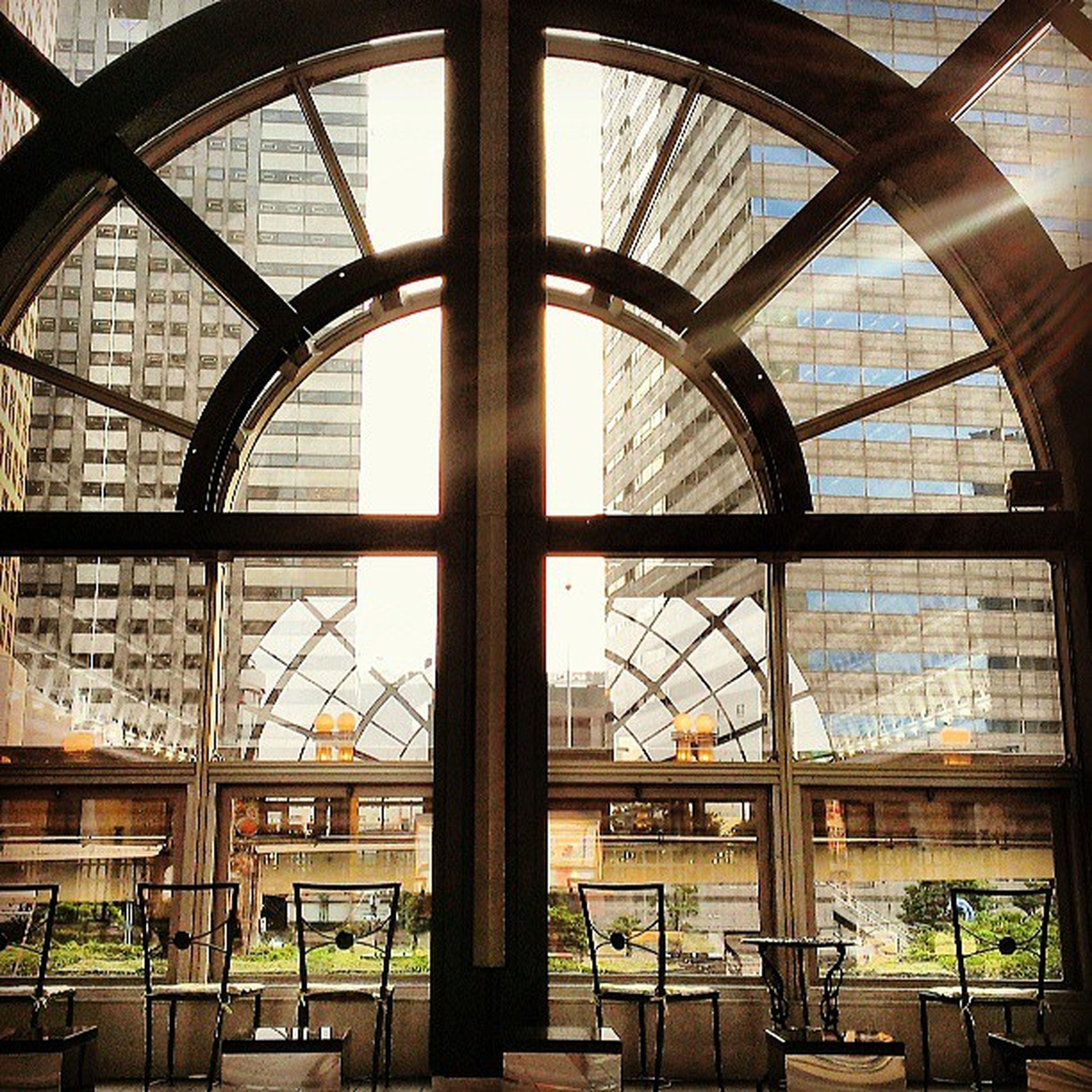 indoors, architecture, built structure, window, glass - material, ceiling, interior, skylight, day, transparent, arch, building exterior, no people, metal, low angle view, building, sky, architectural feature, geometric shape, pattern