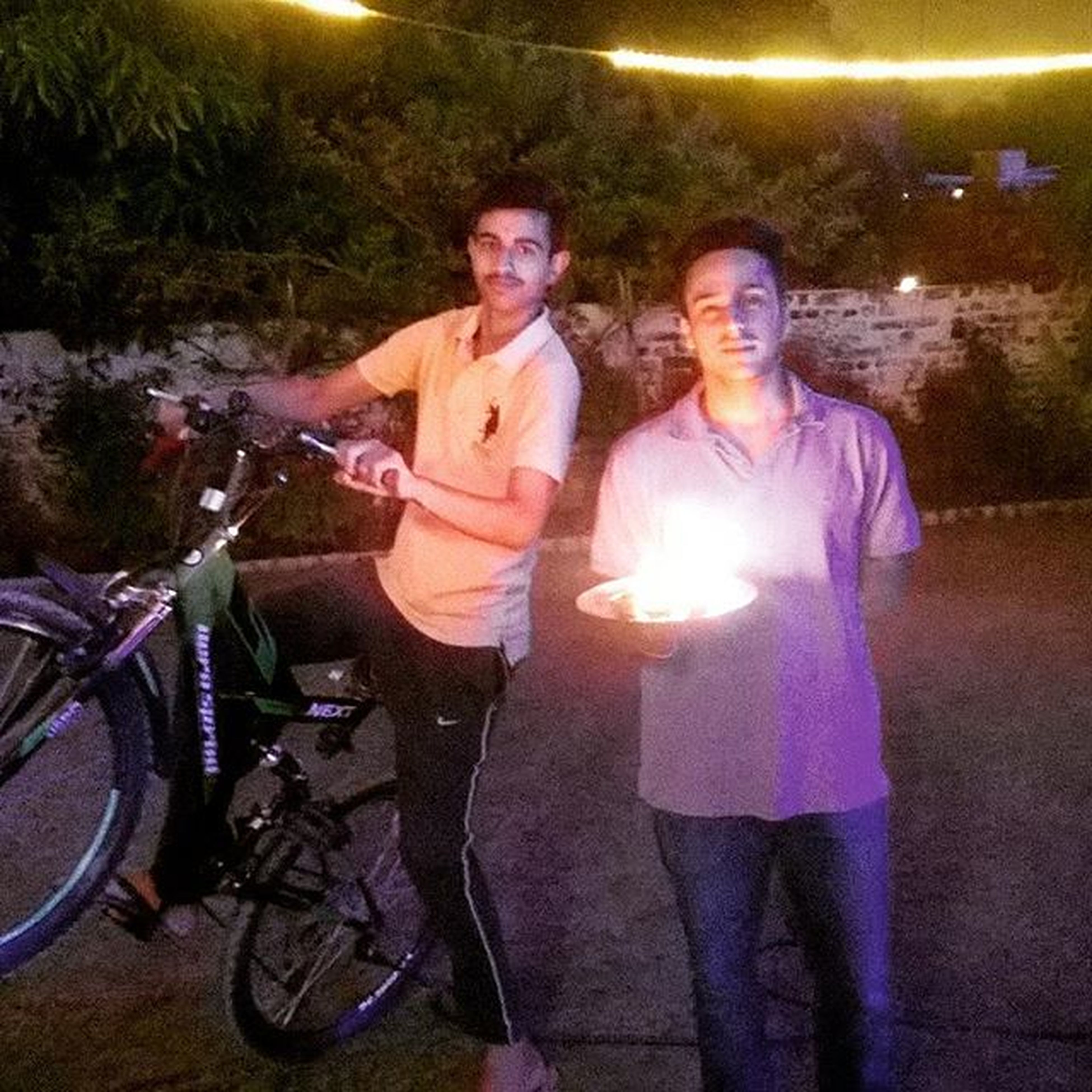 lifestyles, leisure activity, night, casual clothing, illuminated, standing, full length, togetherness, men, young adult, front view, person, bicycle, outdoors, holding, friendship, street
