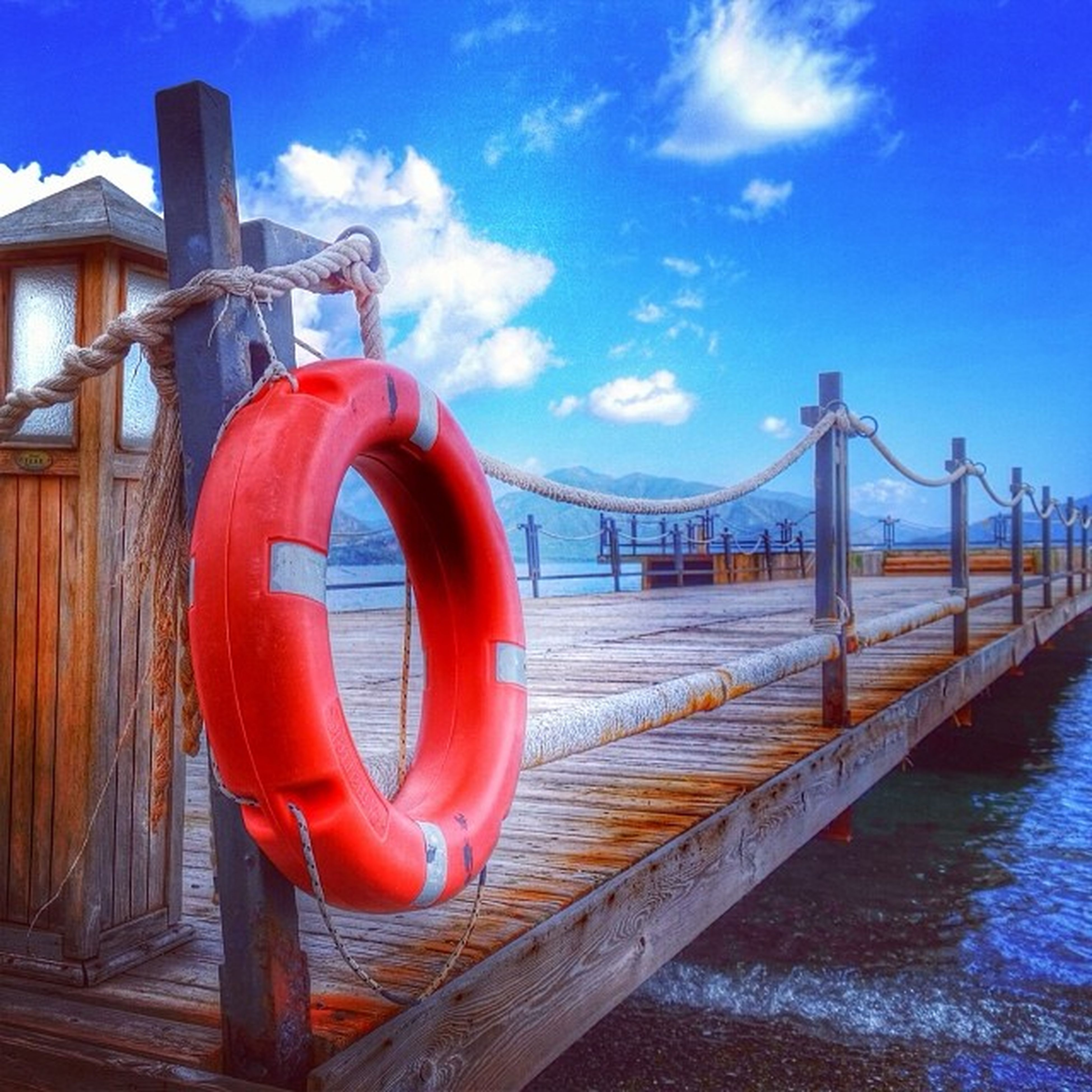 water, built structure, sea, transportation, railing, blue, red, architecture, sky, nautical vessel, pier, mode of transport, safety, bridge - man made structure, metal, connection, river, outdoors, boat, wood - material