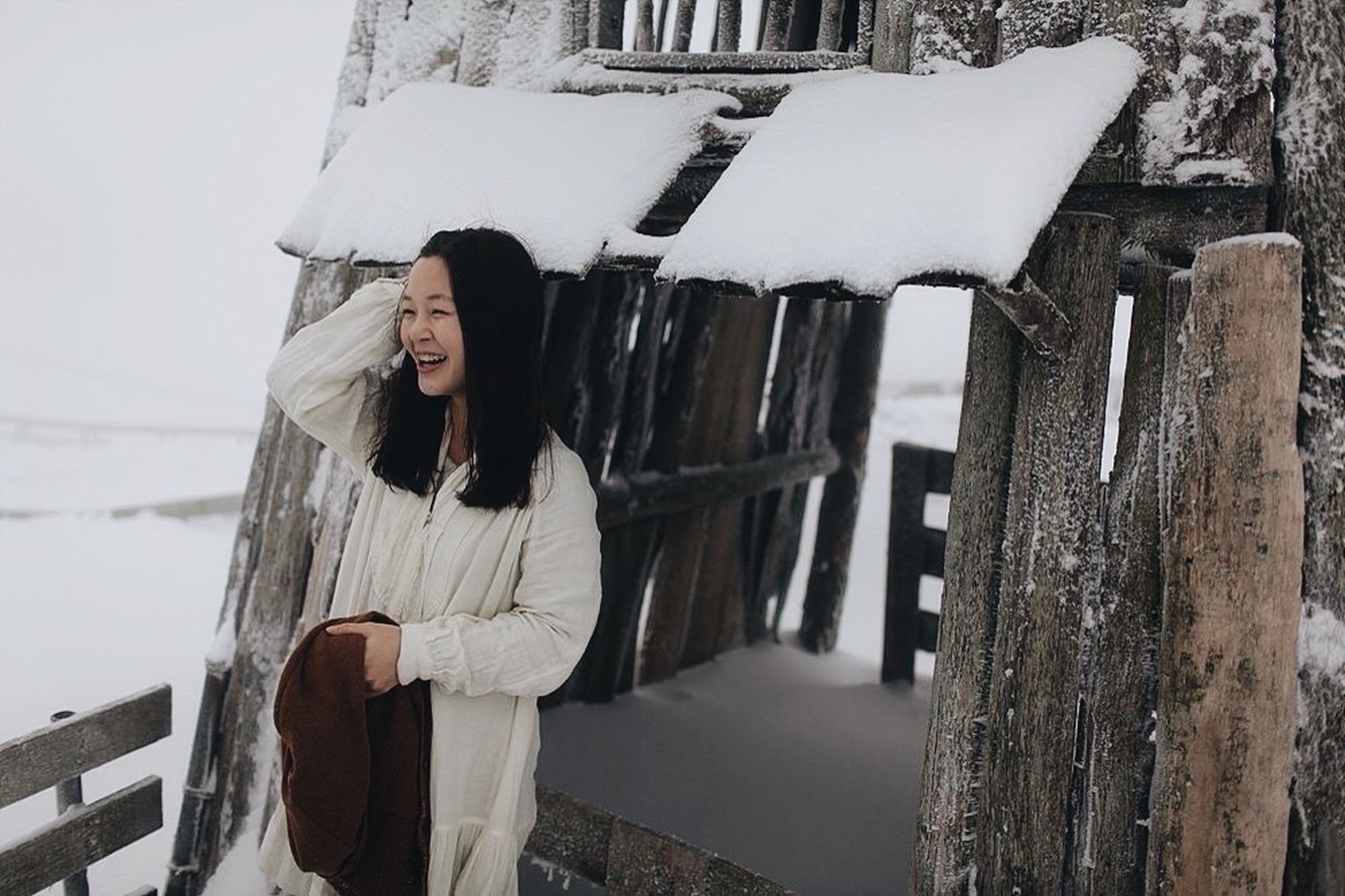 winter, snow, cold temperature, season, wood - material, covering, focus on foreground, day, weather, lifestyles, built structure, outdoors, building exterior, frozen, rear view, standing, warm clothing, white color