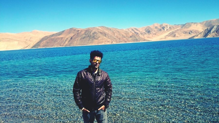Incredible Ladakh! Standing Scenics Blue Mountain Clear Sky Water Leisure Activity Lifestyles Casual Clothing Three Quarter Length Tranquil Scene Mountain Range Beauty In Nature Person Vacations Tranquility Sea Nature Looking At Camera Young Adult