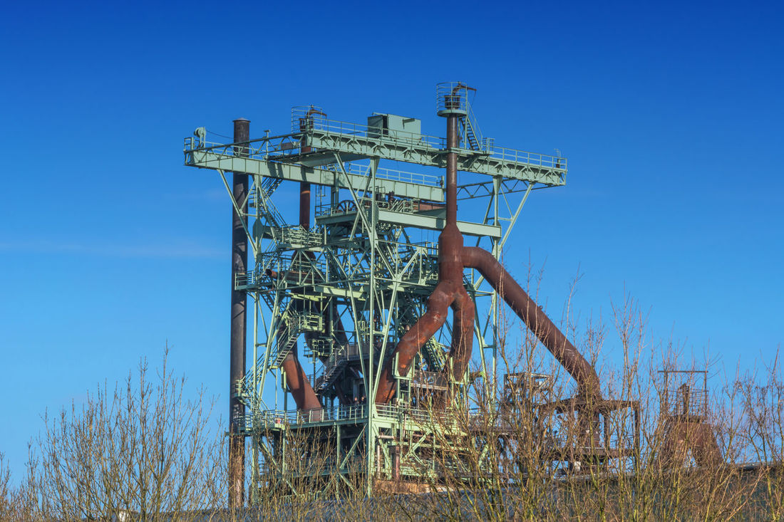 View blast furnace of an old steel mill before blue sky. Blue Clear Sky Day Drilling Rig Eisenwerk Industrial Oven Industry No People Offshore Platform Oil Industry Outdoors Sky Steel Works Steelworks