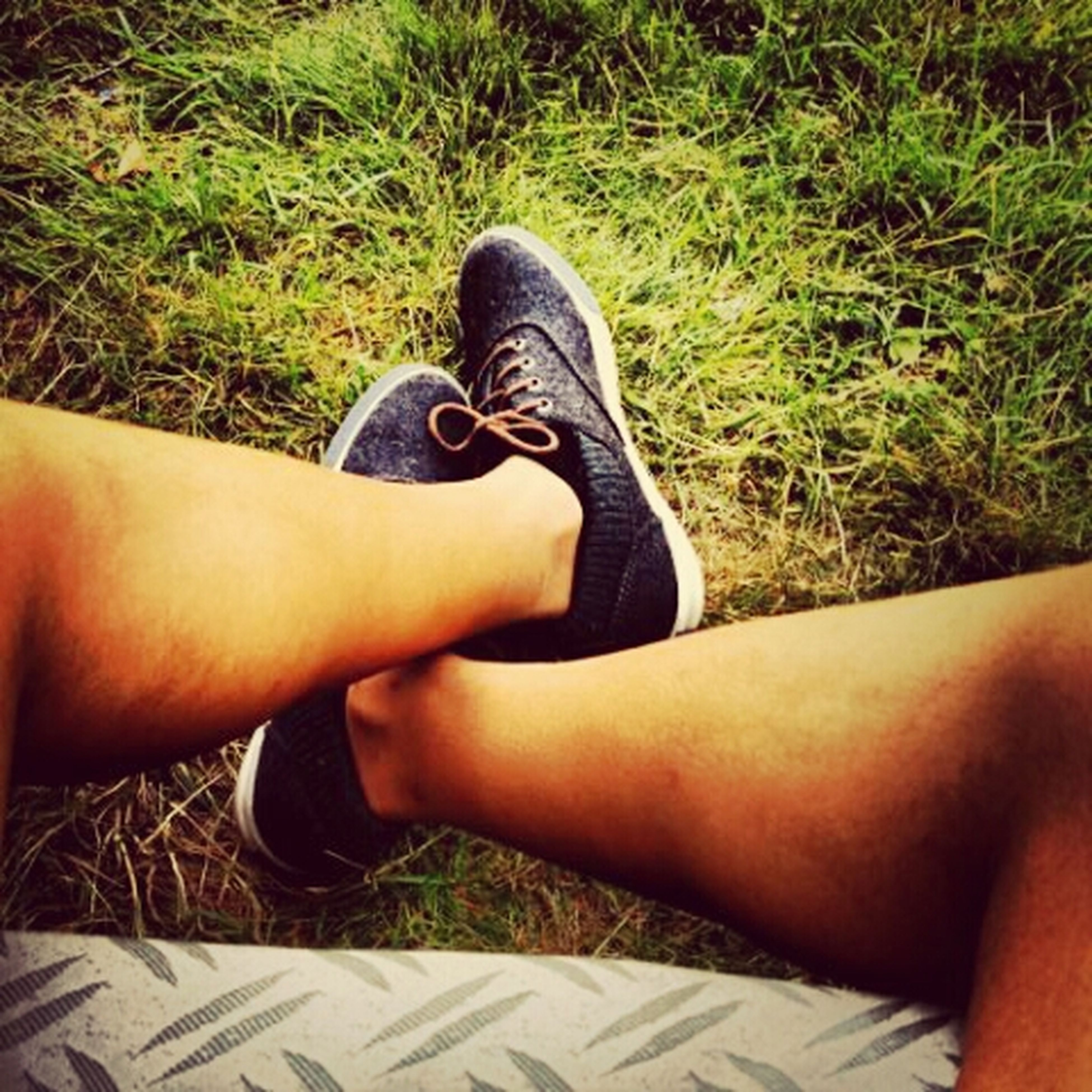 person, low section, personal perspective, lifestyles, leisure activity, shoe, grass, human foot, part of, relaxation, high angle view, legs crossed at ankle, men, footwear, sitting