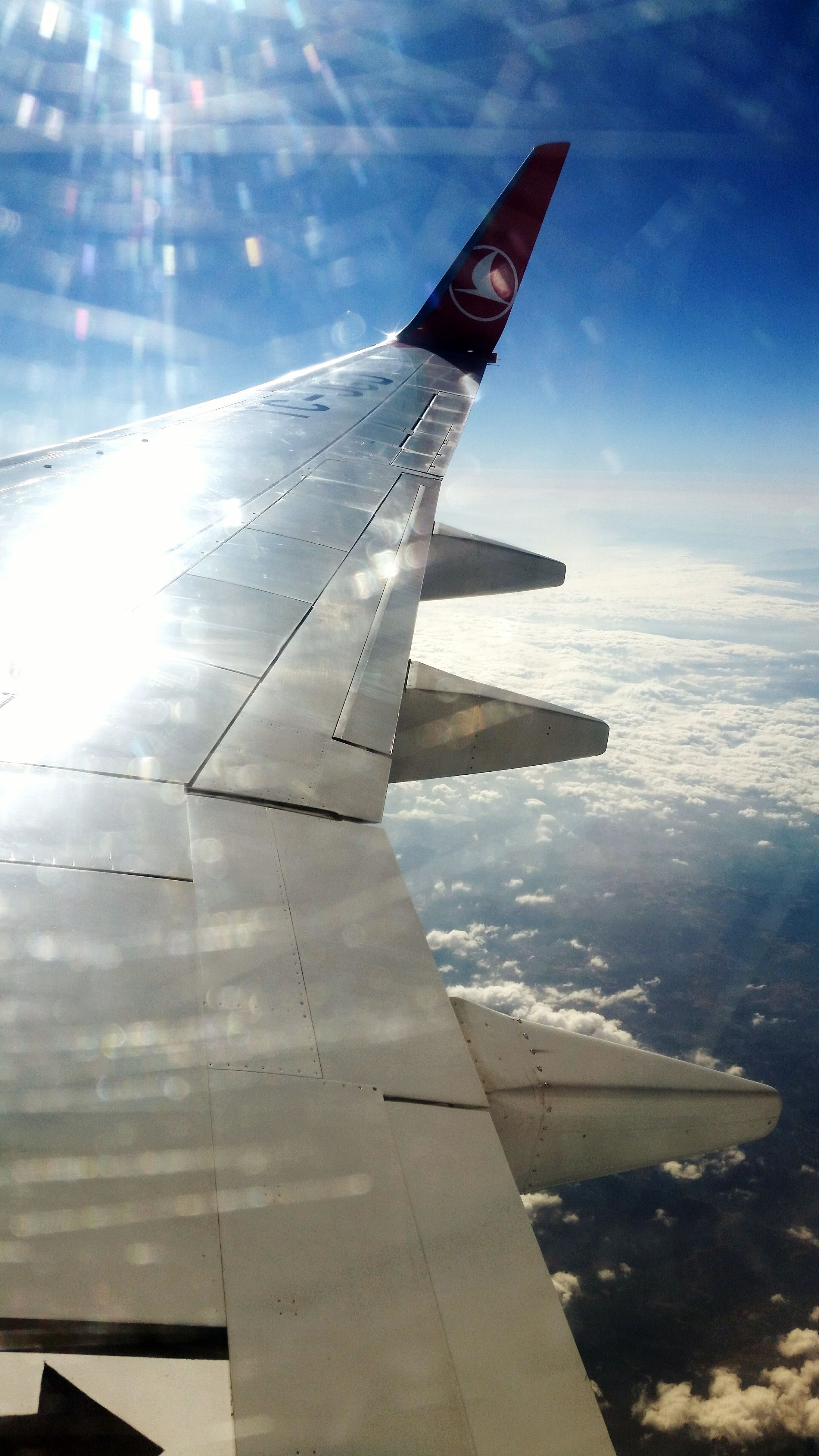aircraft wing, sky, cloud - sky, sunlight, part of, cloud, aerial view, nature, scenics, cropped, beauty in nature, outdoors, sun, day, no people, sunbeam, tranquility, blue, tranquil scene, cloudy, landscape, cloudscape, idyllic, weather