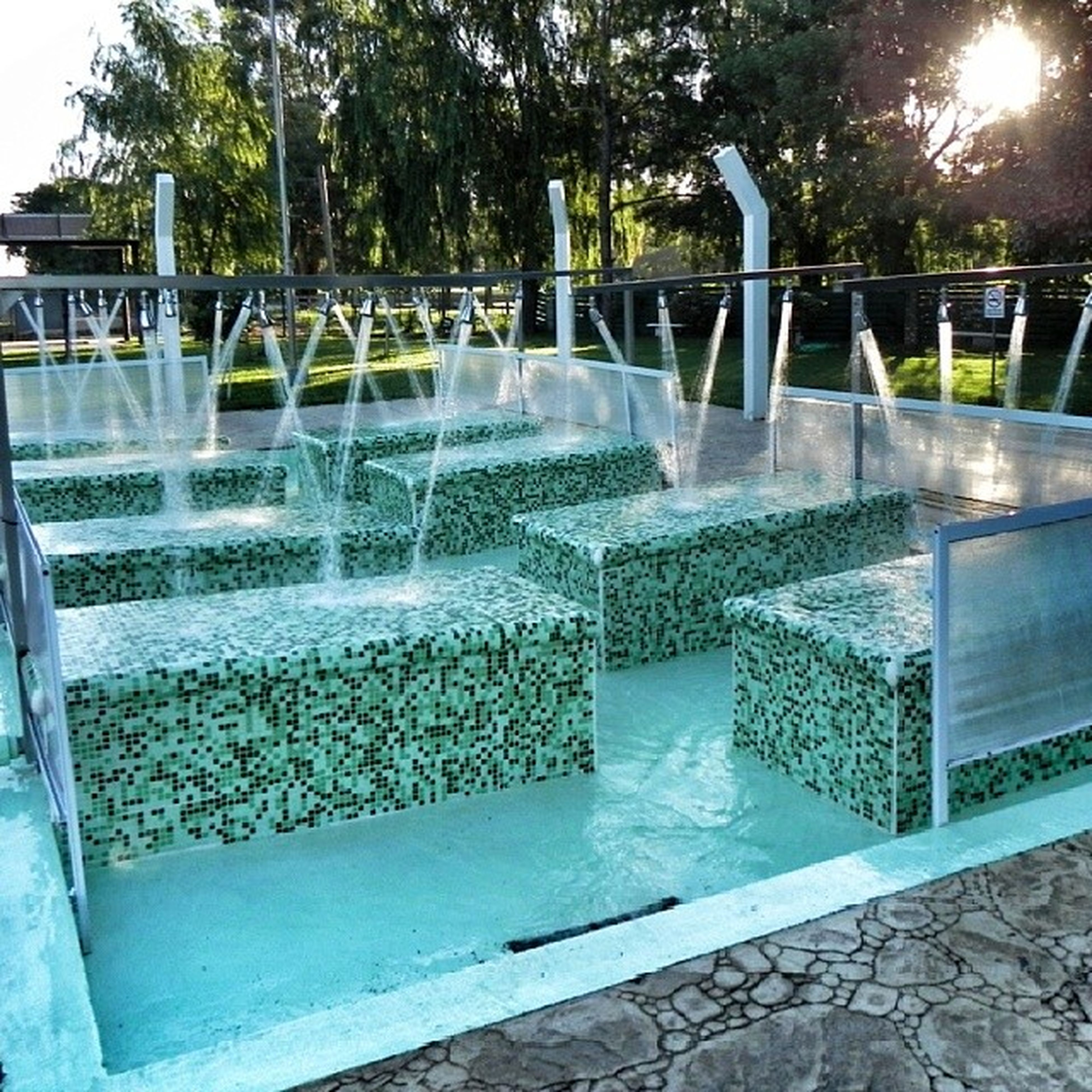 water, railing, fountain, reflection, tree, sunlight, built structure, swimming pool, motion, park - man made space, glass - material, architecture, pond, day, sunbeam, splashing, nature, metal, outdoors, no people