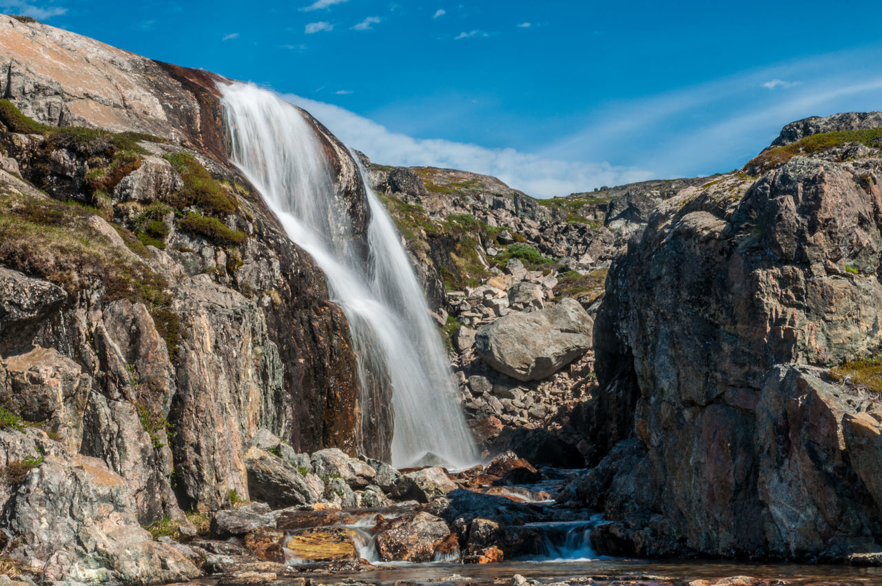 Scenic View Of Waterfall On Rocky Mountain Against Sky