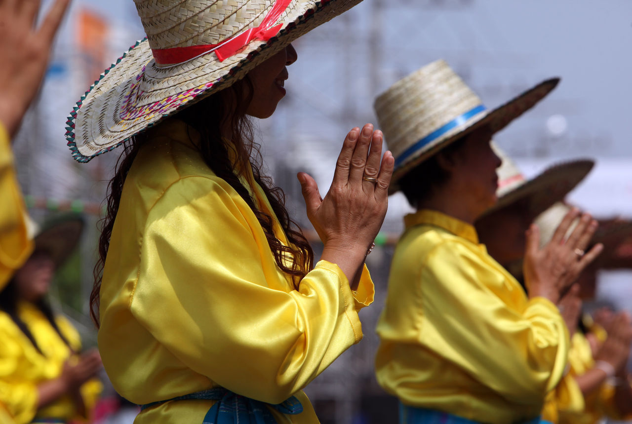 traditional clothing, hat, real people, yellow, cultures, traditional dancing, lifestyles, traditional festival, men, costume, tradition, focus on foreground, leisure activity, women, outdoors, performance, day, headwear