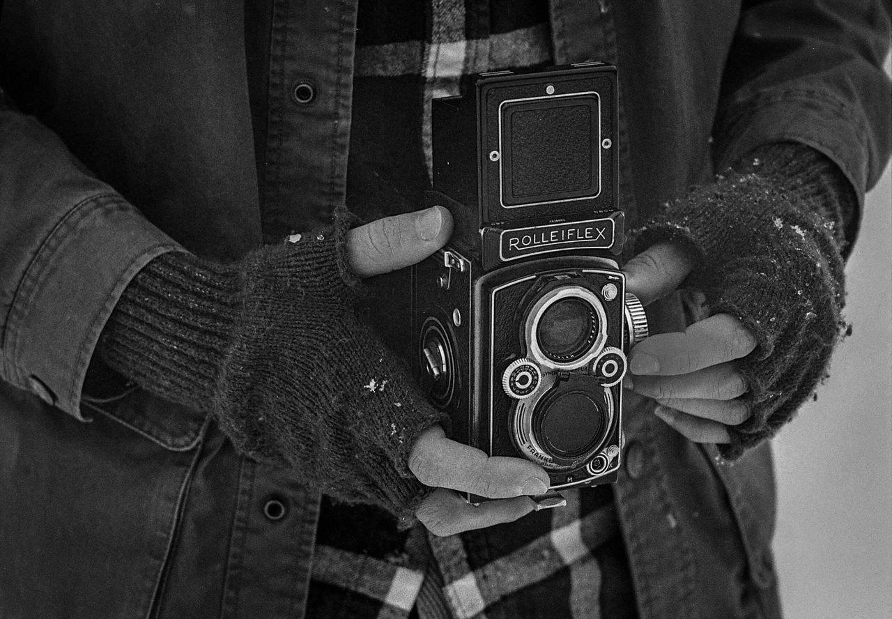 midsection, real people, camera - photographic equipment, holding, technology, photography themes, photographing, men, one person, leisure activity, standing, outdoors, close-up, lifestyles, weapon, day, digital single-lens reflex camera, human hand, warm clothing, adult, adults only, people