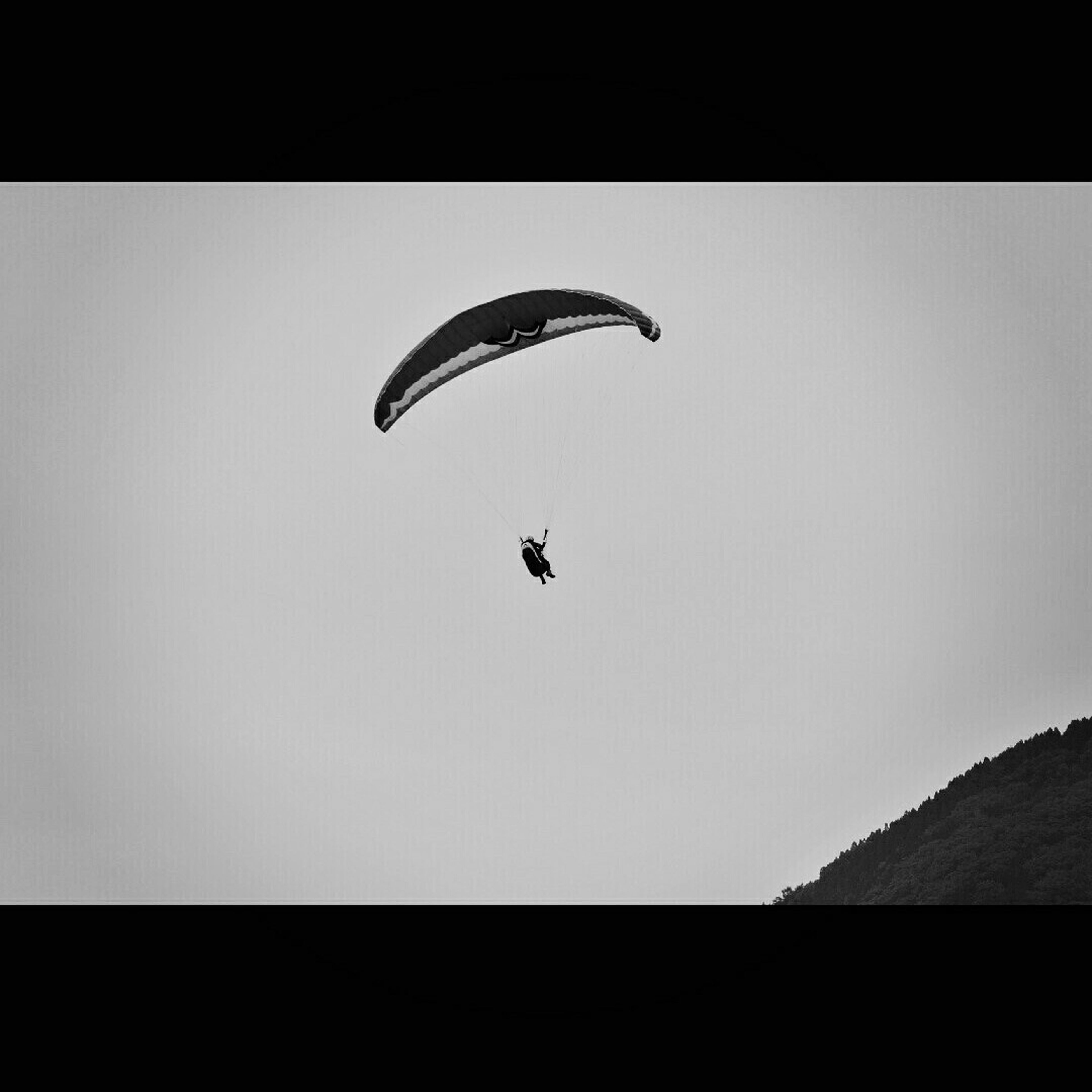 flying, mid-air, extreme sports, transportation, adventure, parachute, low angle view, paragliding, leisure activity, clear sky, copy space, silhouette, exhilaration, lifestyles, mode of transport, air vehicle, unrecognizable person, freedom