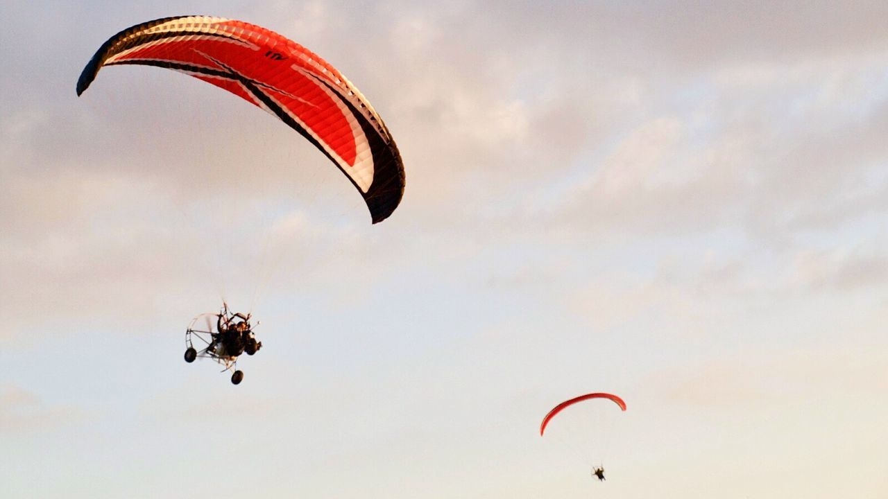 parachute, extreme sports, adventure, paragliding, mid-air, flying, leisure activity, exhilaration, gliding, unrecognizable person, skydiving, parasailing, real people, risk, freedom, low angle view, sport, lifestyles, sky, day, outdoors, nature, stunt person, people