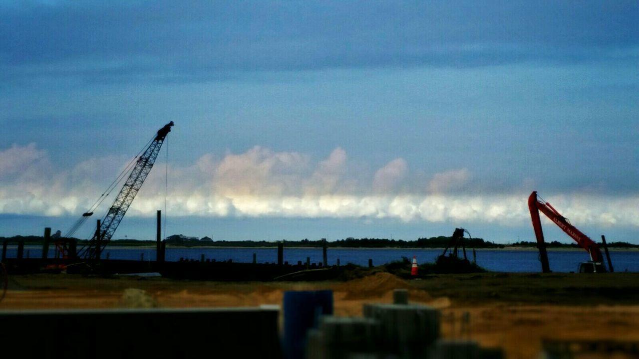 sky, construction site, development, crane - construction machinery, no people, crane, cloud - sky, built structure, industry, architecture, outdoors, nature, sea, day, nautical vessel, water, oil pump